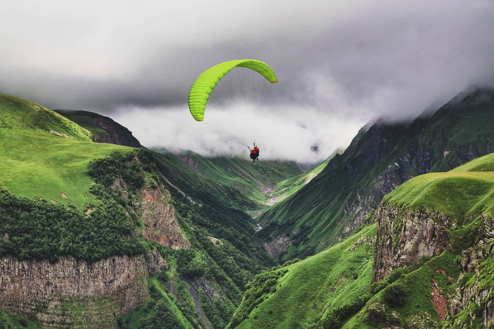 person paragliding near mountain range