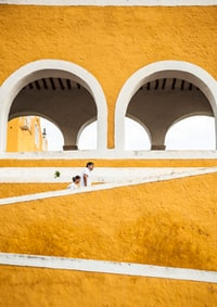 man and woman walking up on yellow stairs