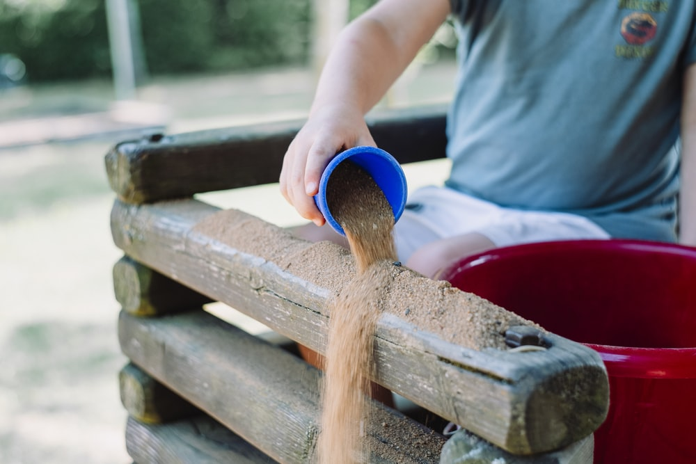 toddler pouring sand in brown wooden fence