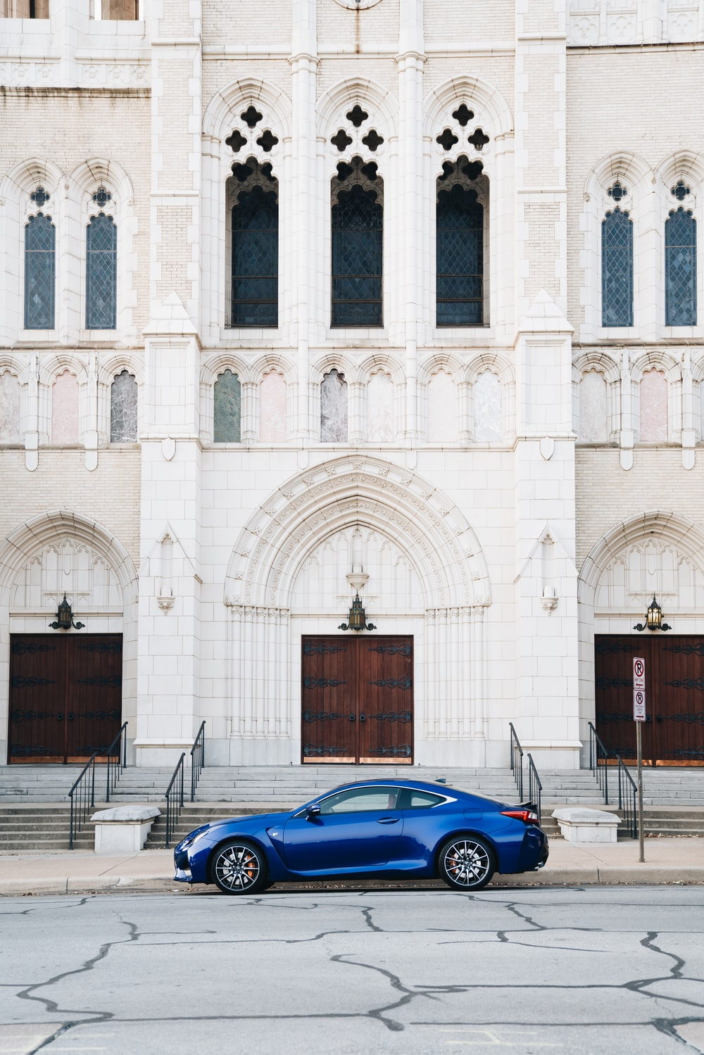 blue coupe parked in front of cathedral