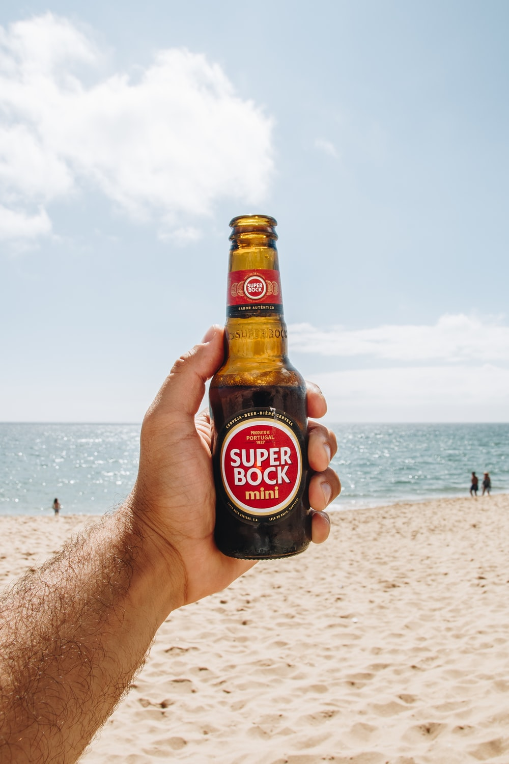 person holding opened Super Bock bottle