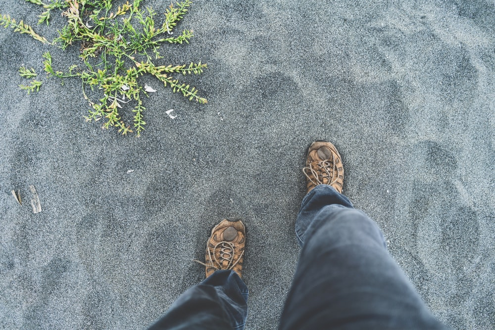 person standing on gray sand