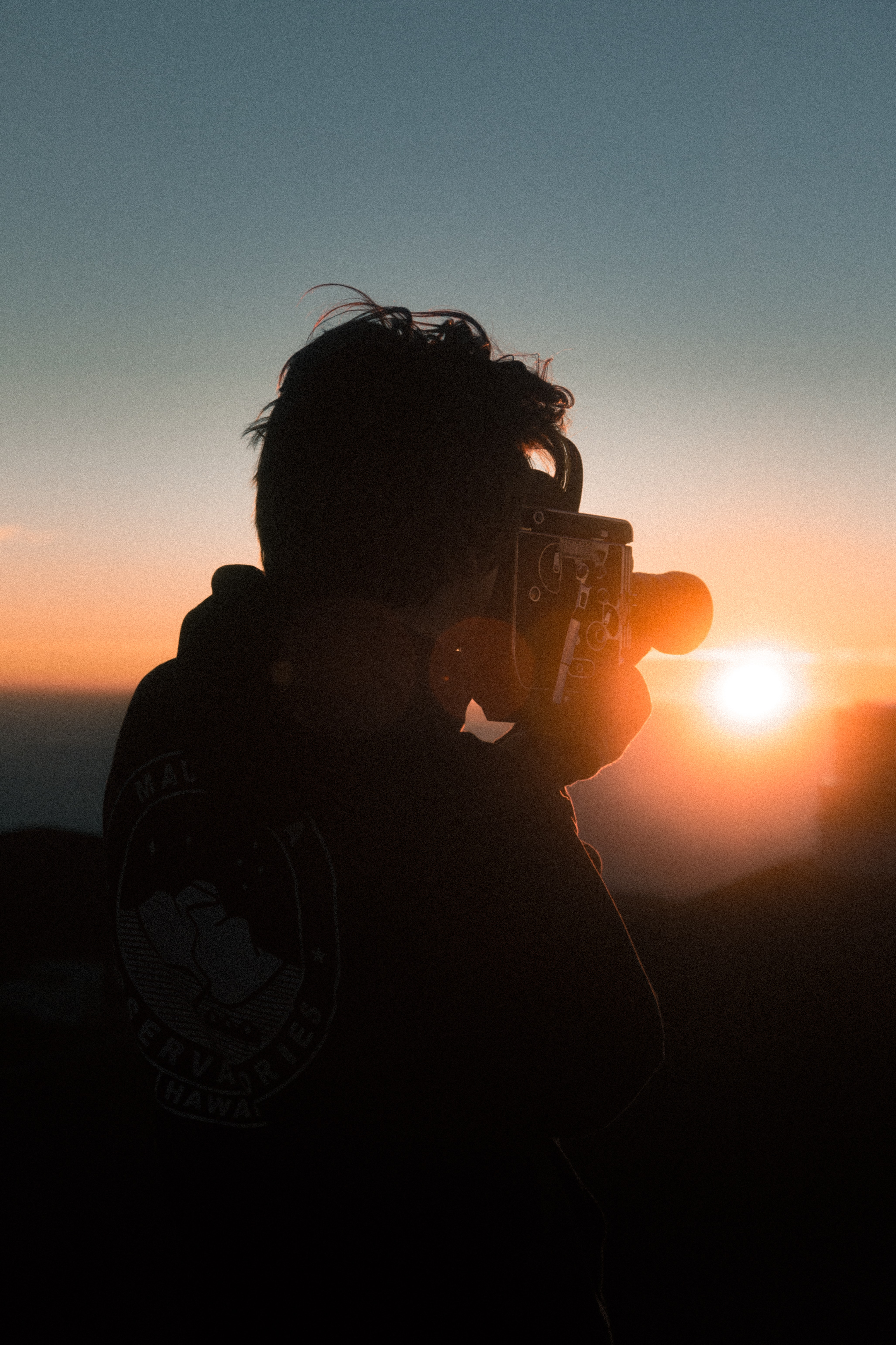 man holding classic camera during golden hour