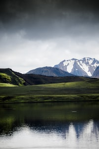body of water beside hill grass and mountains at the distance