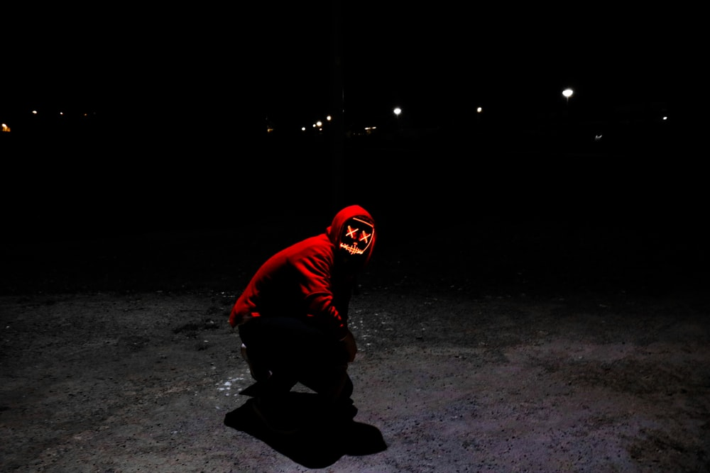 man wearing red hoodie squating on pavement