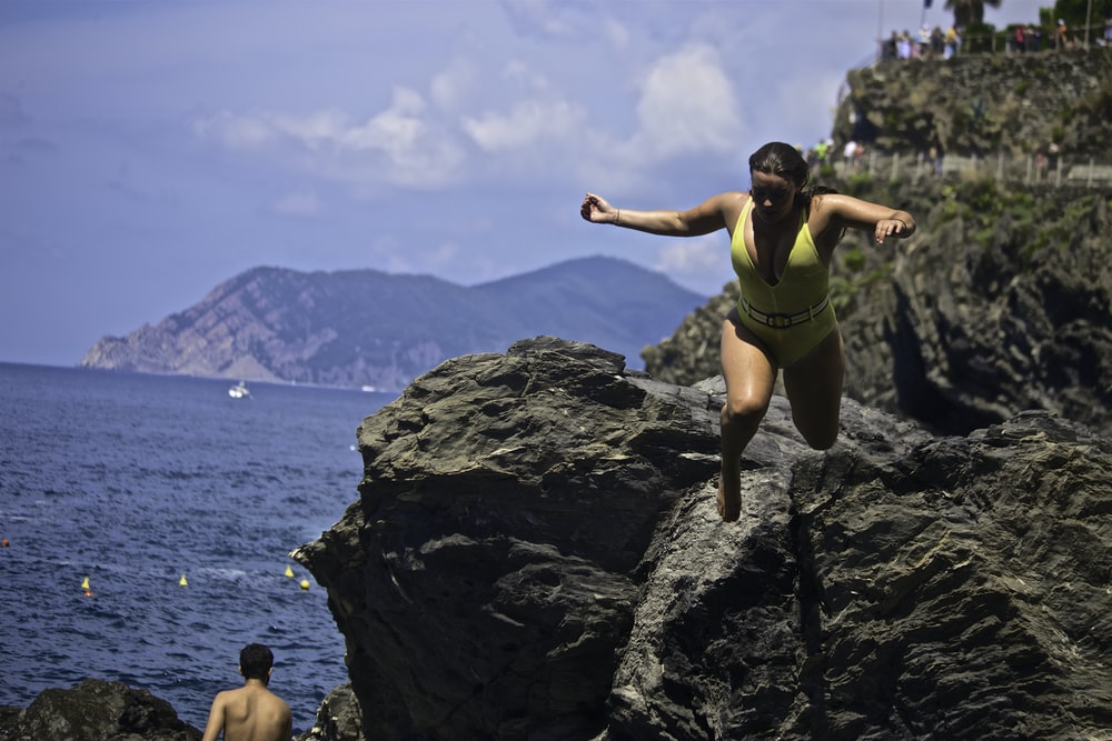 time lapse photography of woman wearing one-piece swimsuit jumping from cliff