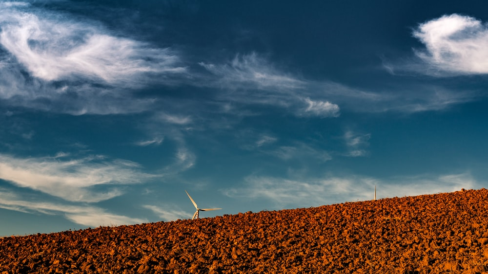 white windmill under cloudy sky