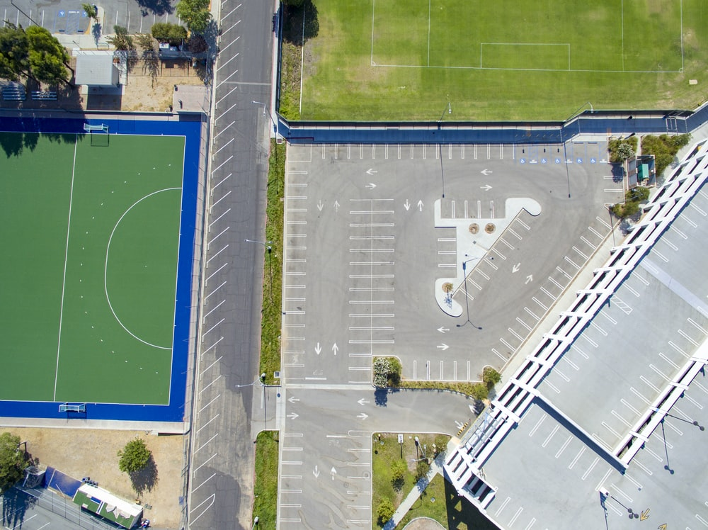 aerial photo of gray concrete pavements near field and tress