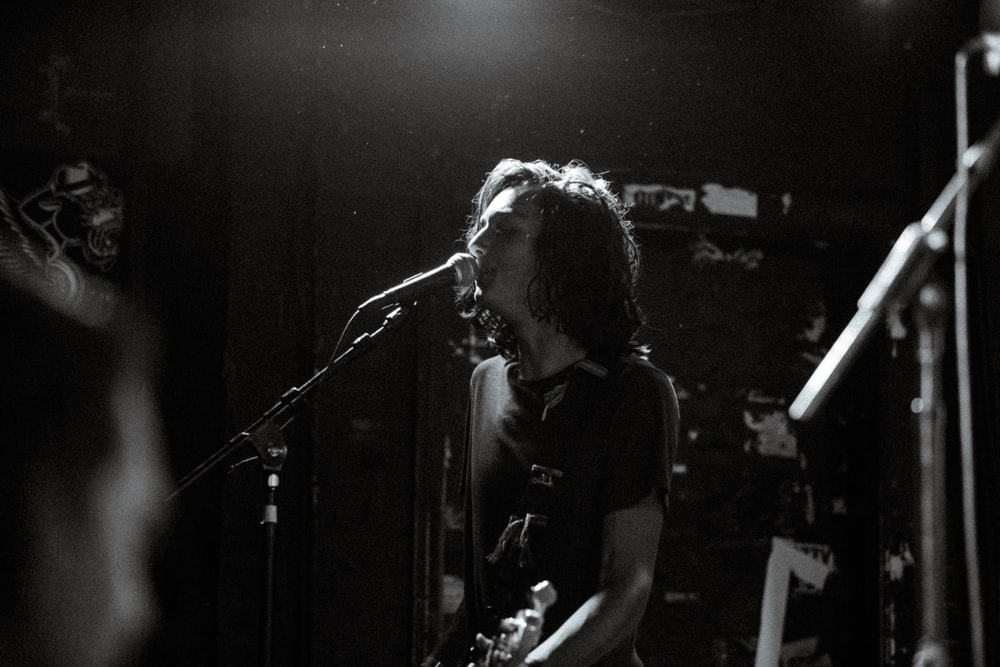 greyscale photo of man singing while holding guitar