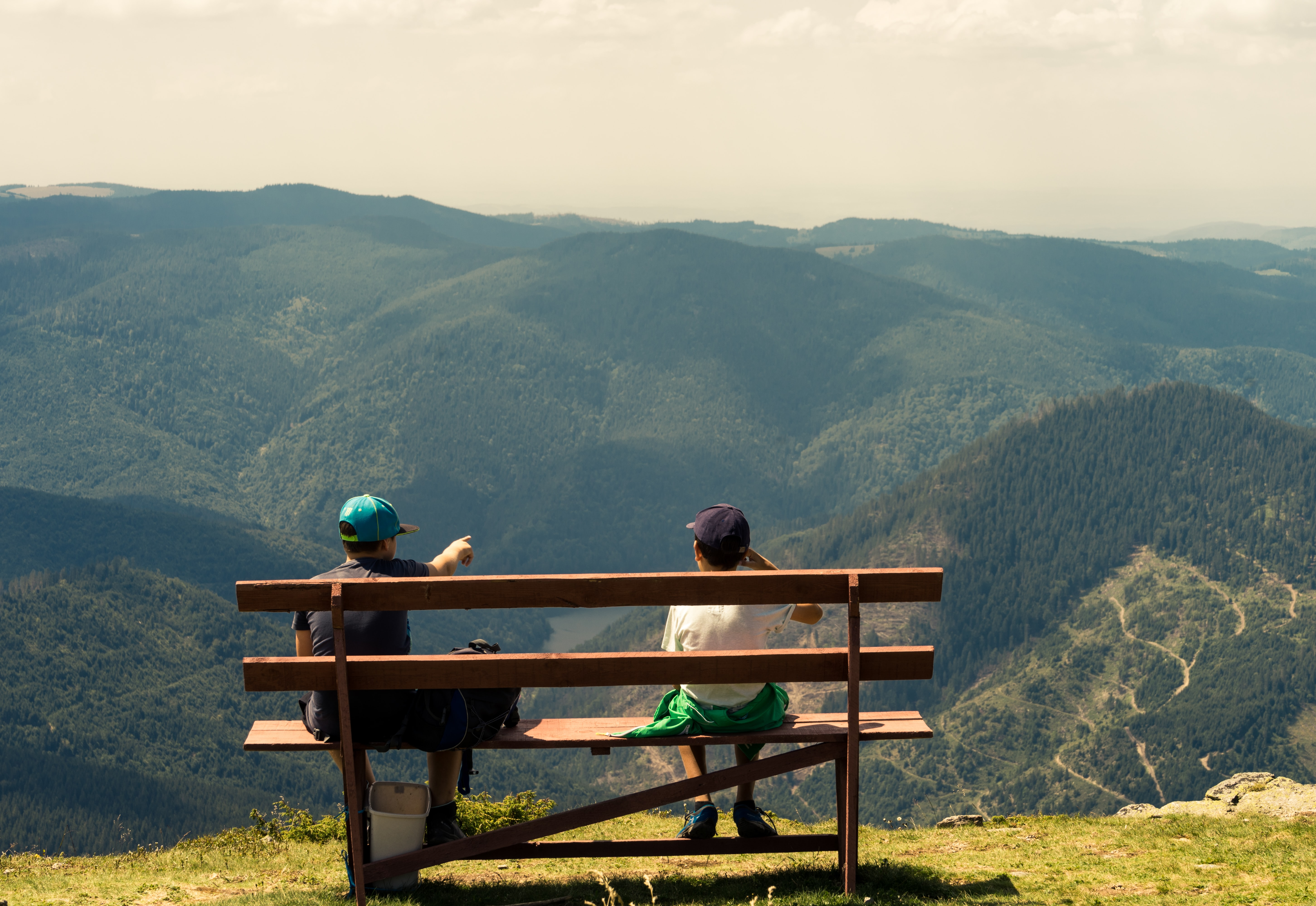 two boys sitting on brown bench