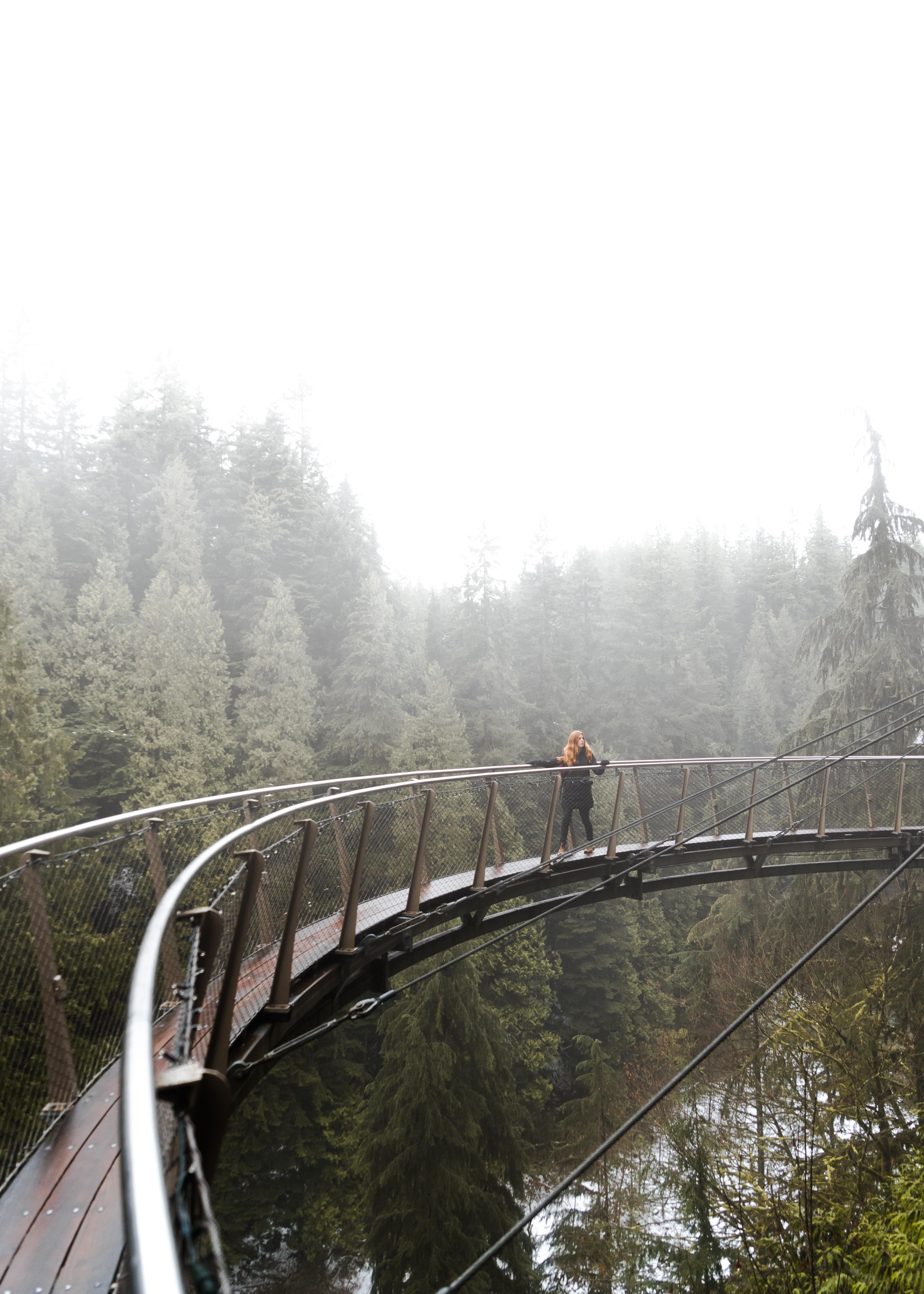 woman walking on brown bridge during daytime