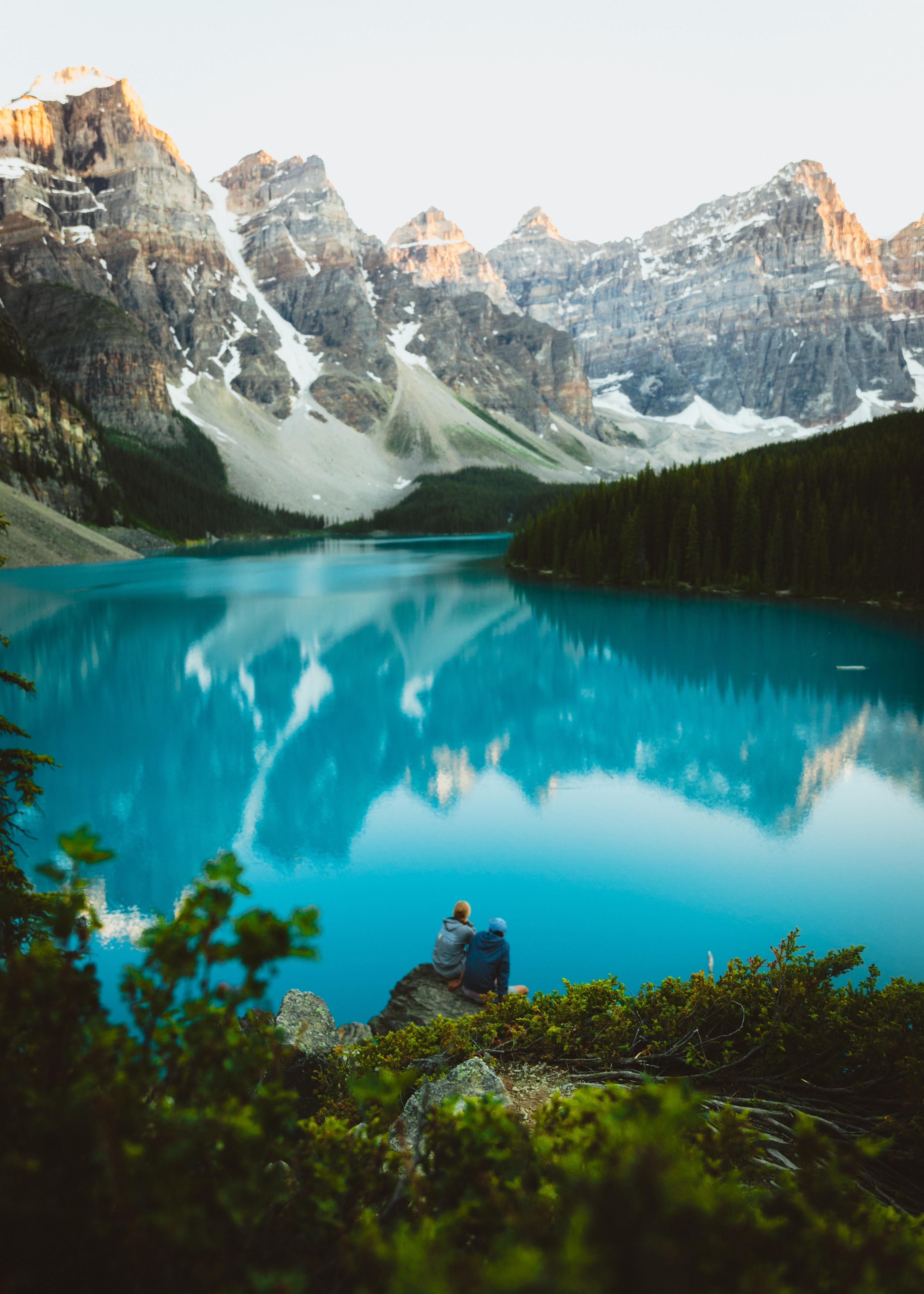 two man sitting on rock watching lake