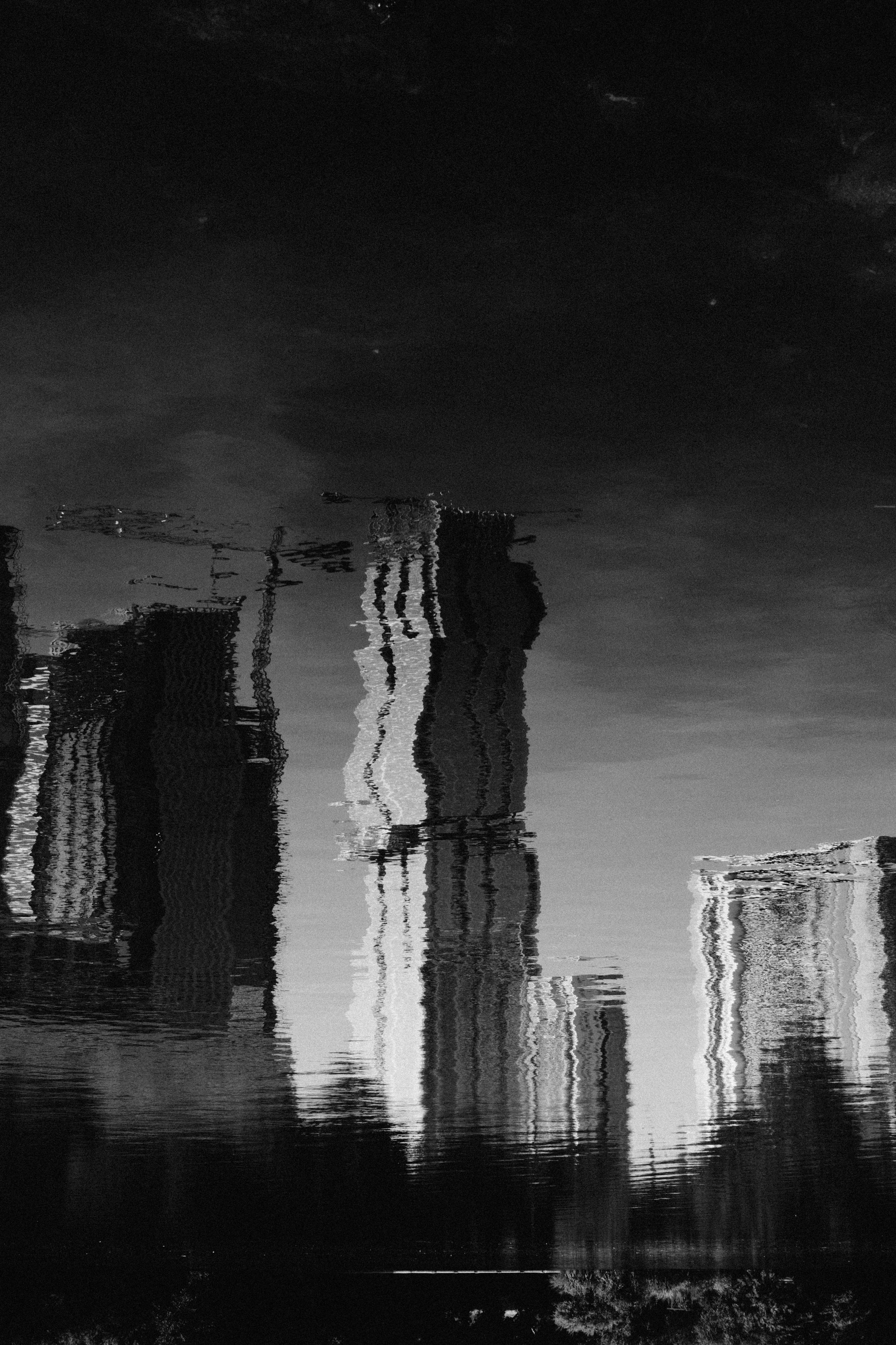 grayscale photo of reflection of buildings in water