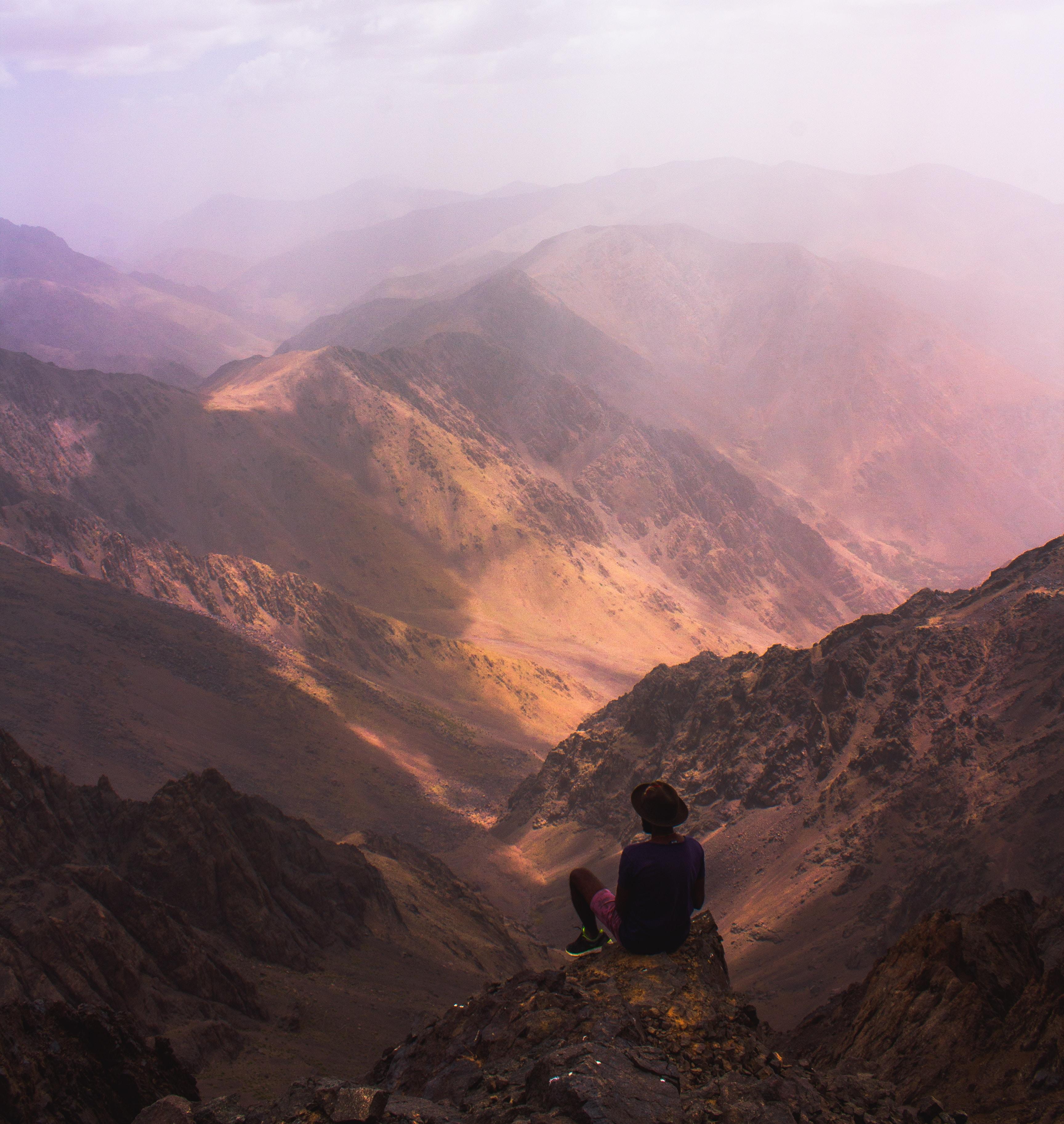 man sitting on mountain edge