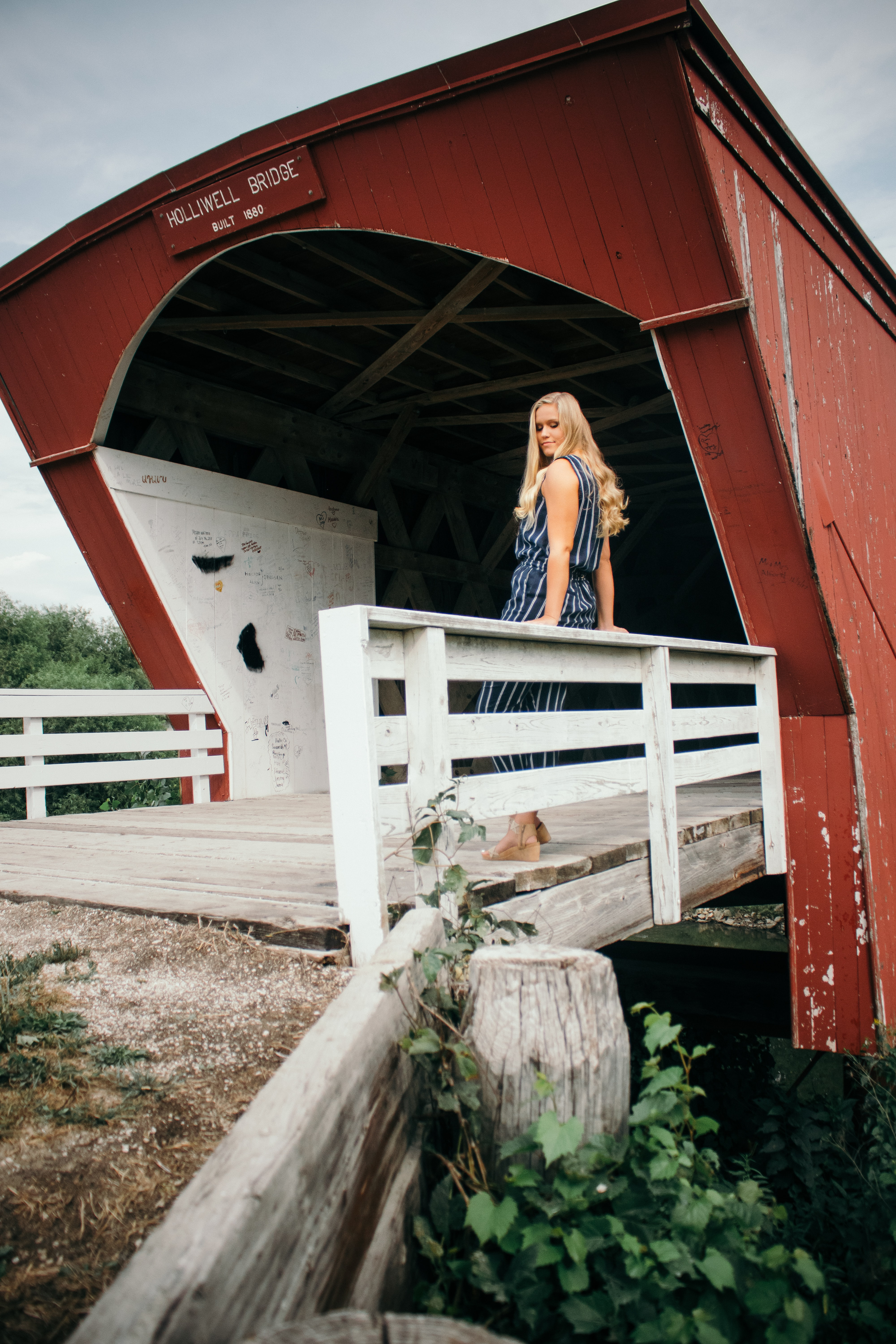 woman standing on gray wooden bridge during daytime