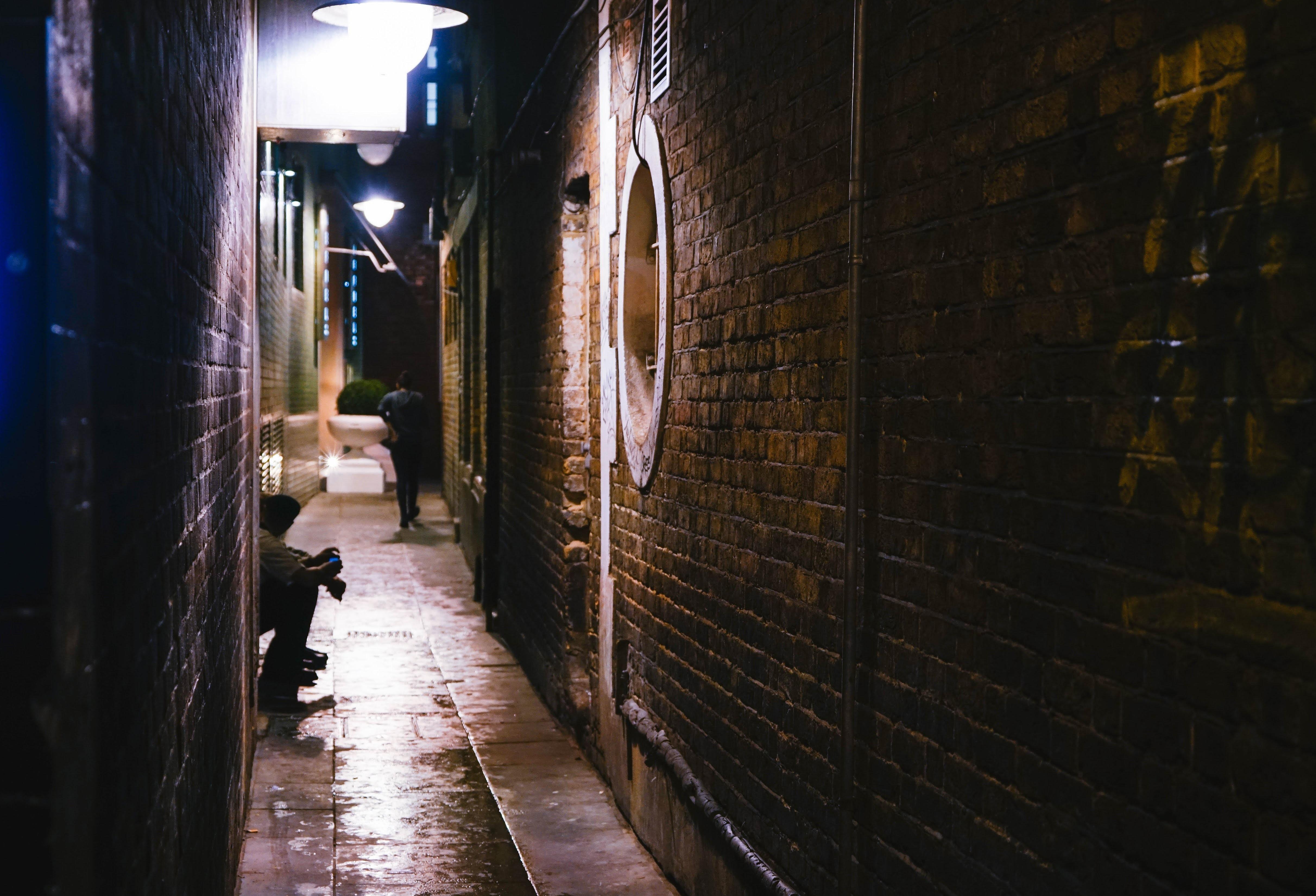 person sitting on road between buildings