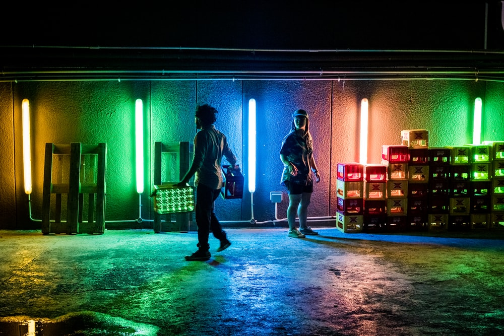 two person standing near green and blue neon lights