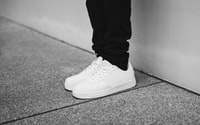 person wearing pair of white sneakers standing near wall