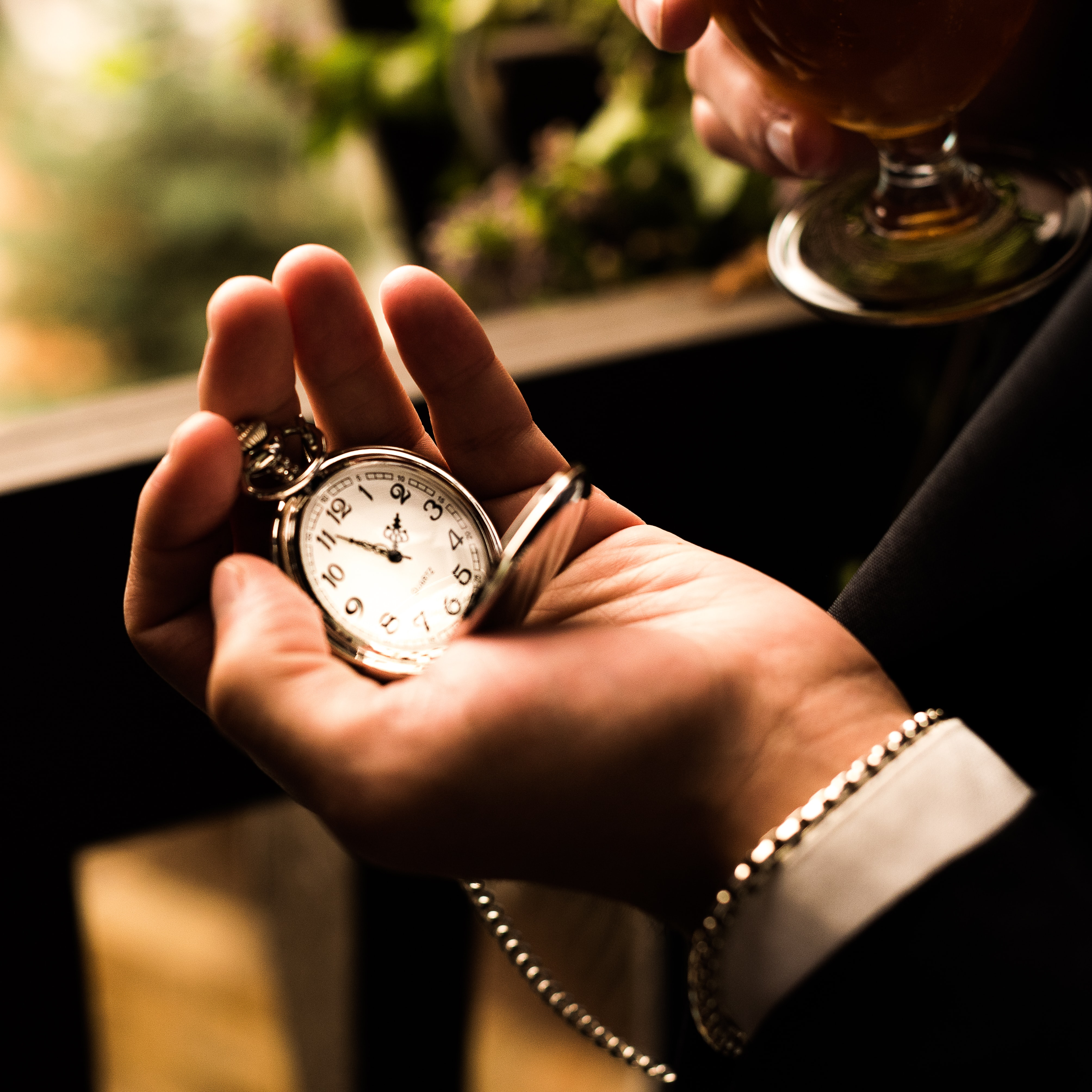 person holding silver-colored pocket watch