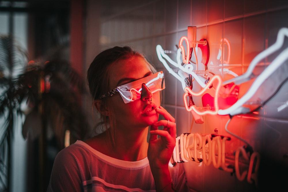 woman standing beside lighted neon lights
