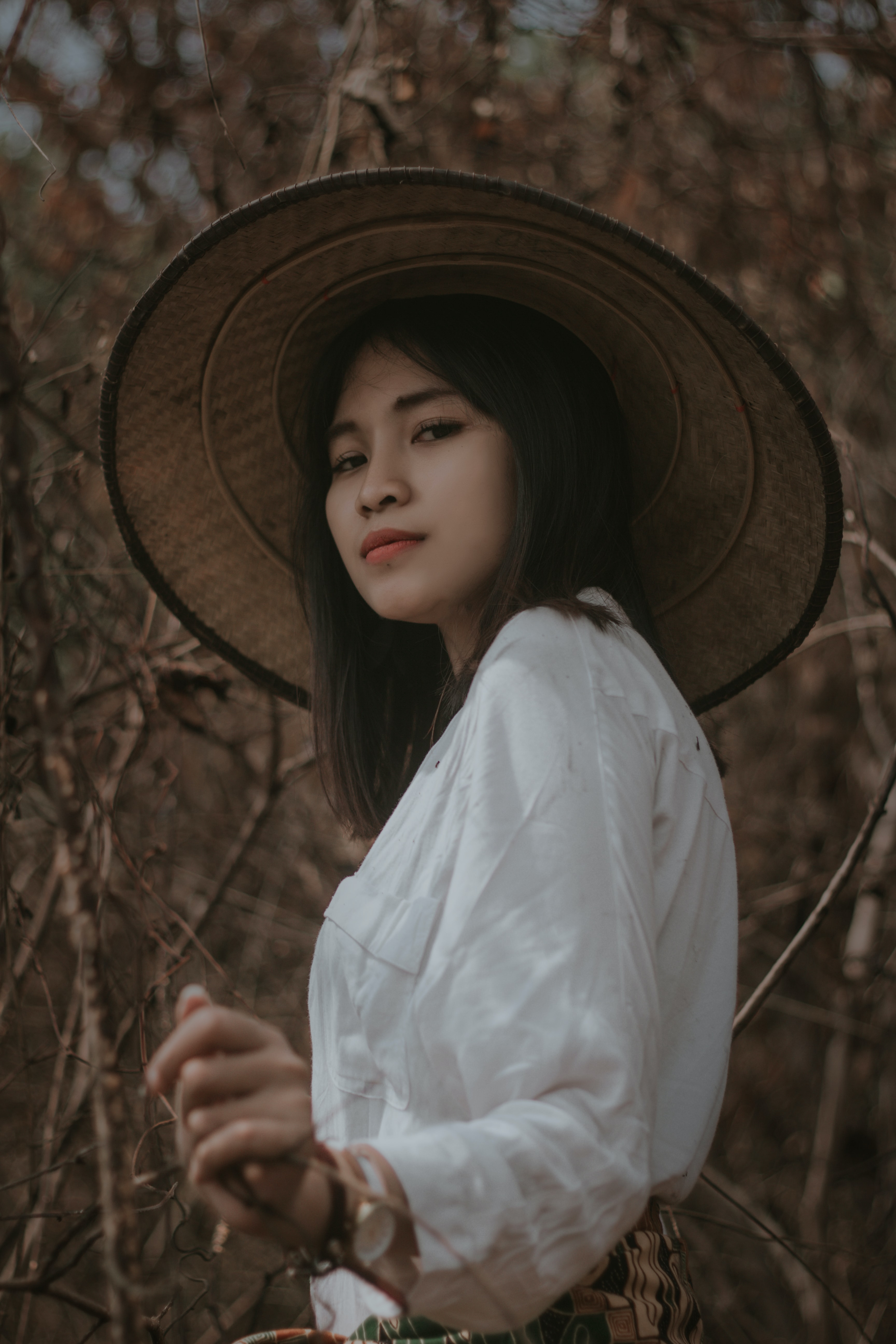 woman wearing conical hat surrounded by trees