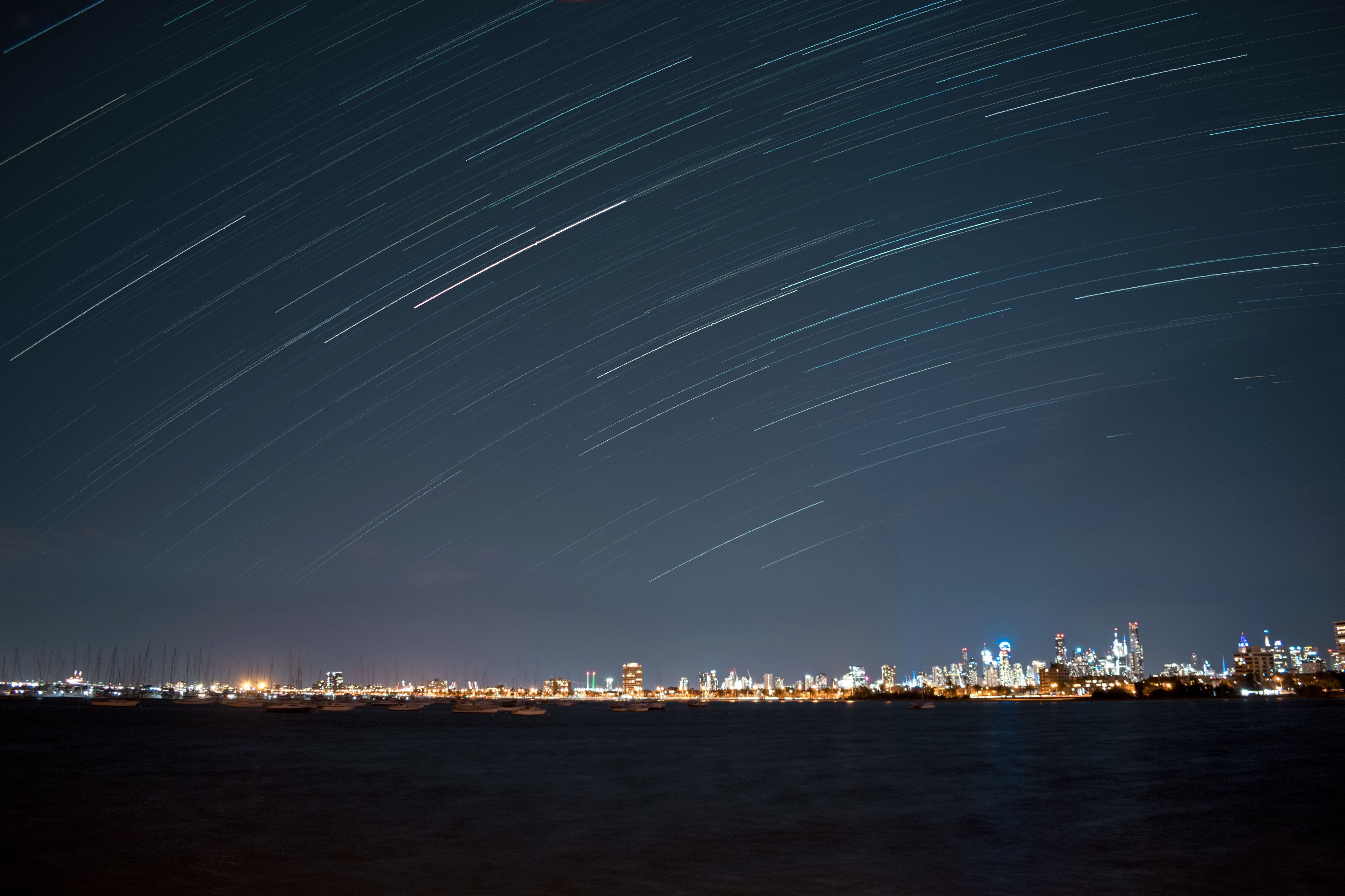 time lapse photography of meteor shower above cityscape