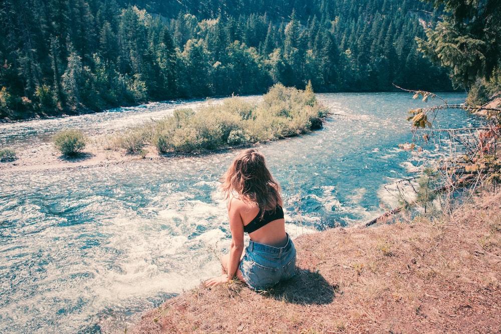 woman wearing blue denim shorts watching the body of water
