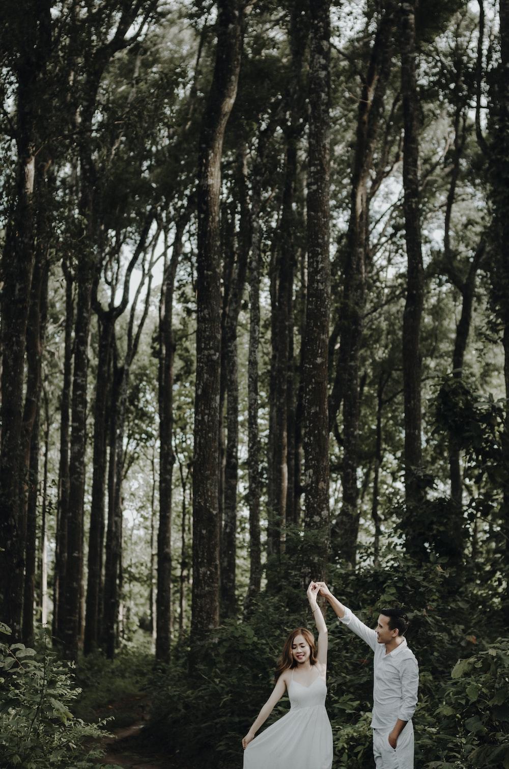 male and female dancing near tree