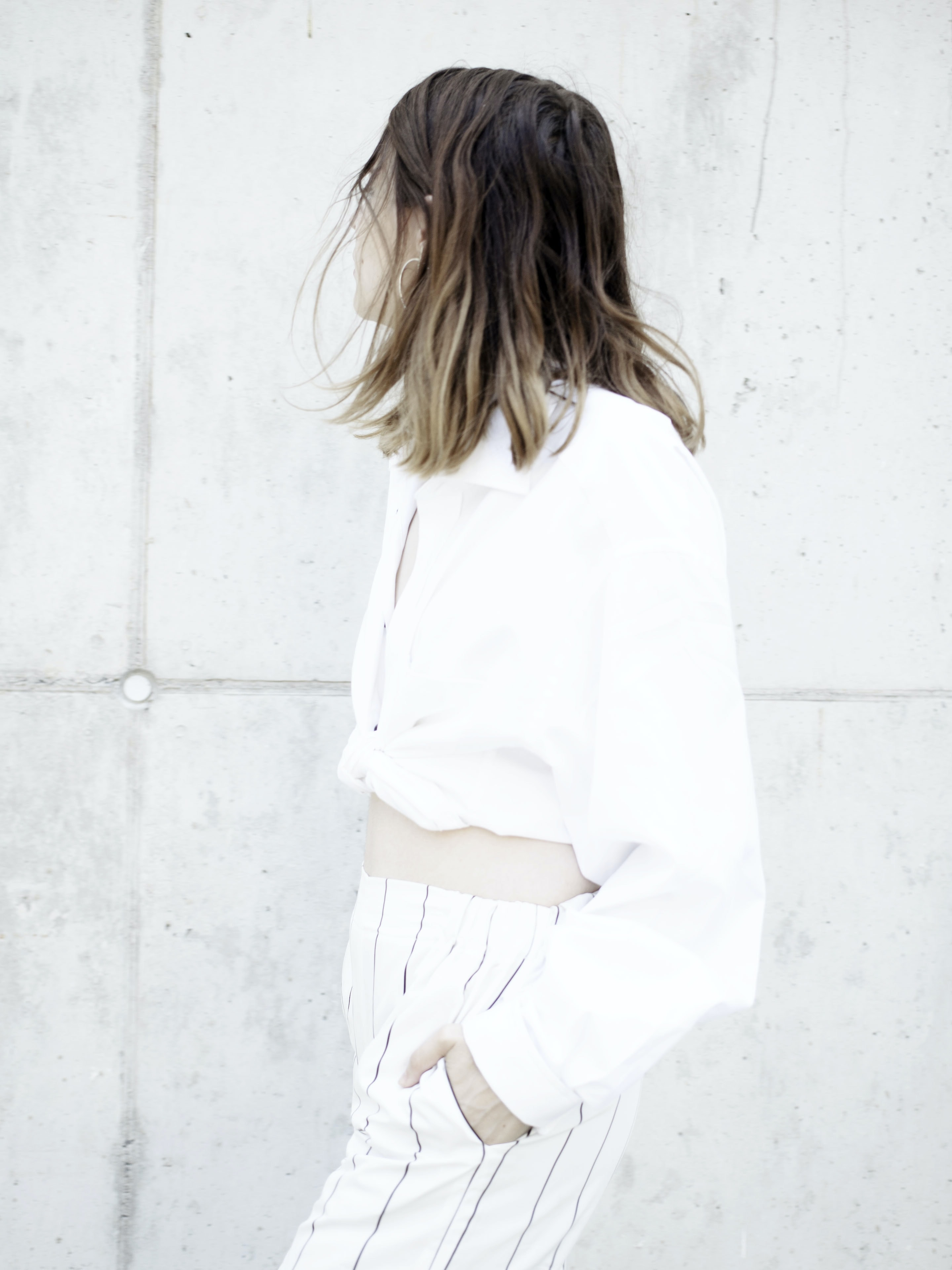 woman wearing white shirt and pants standing beside wall looking sideways