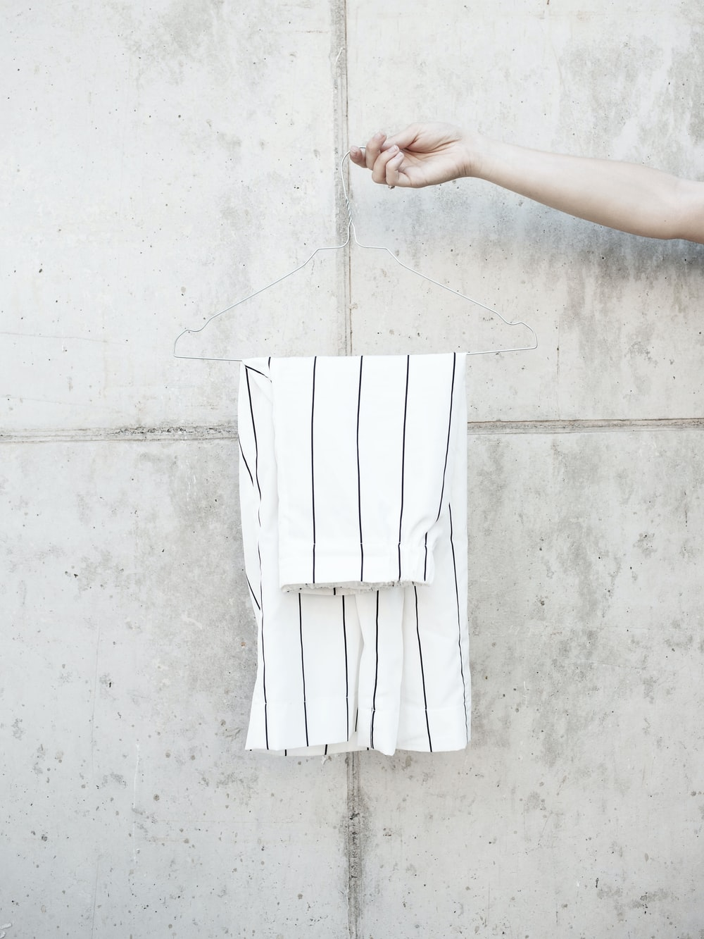 person holding hanger with white shorts