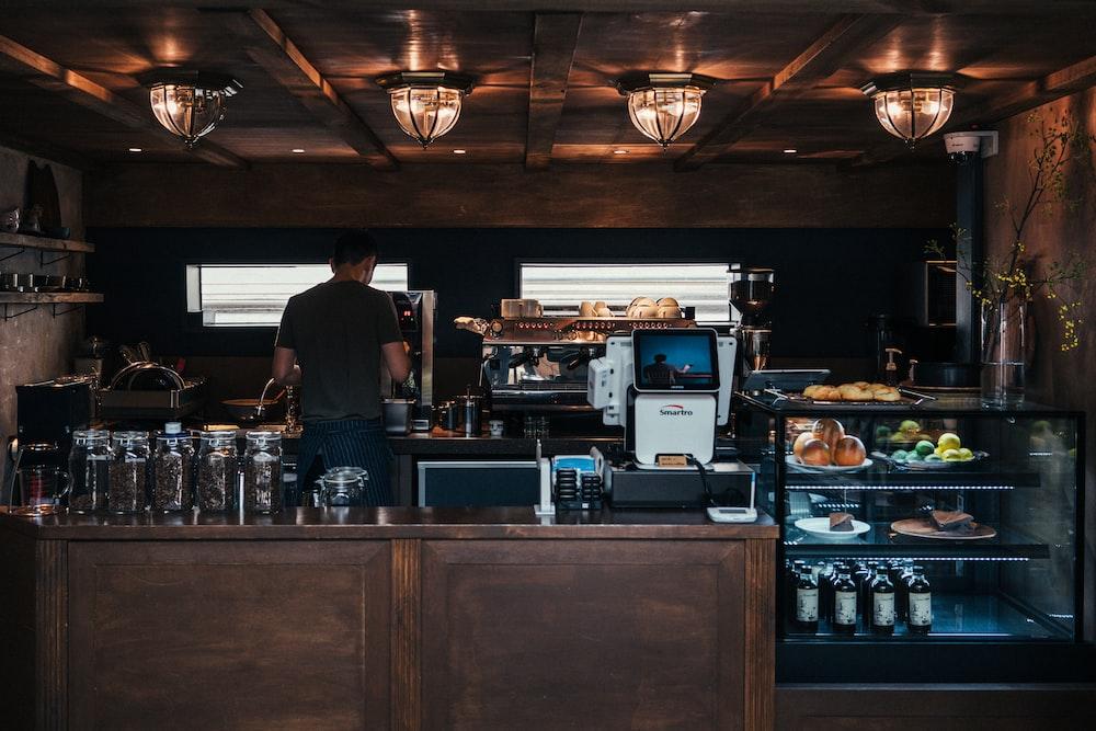 man facing coffeemaker at cafe