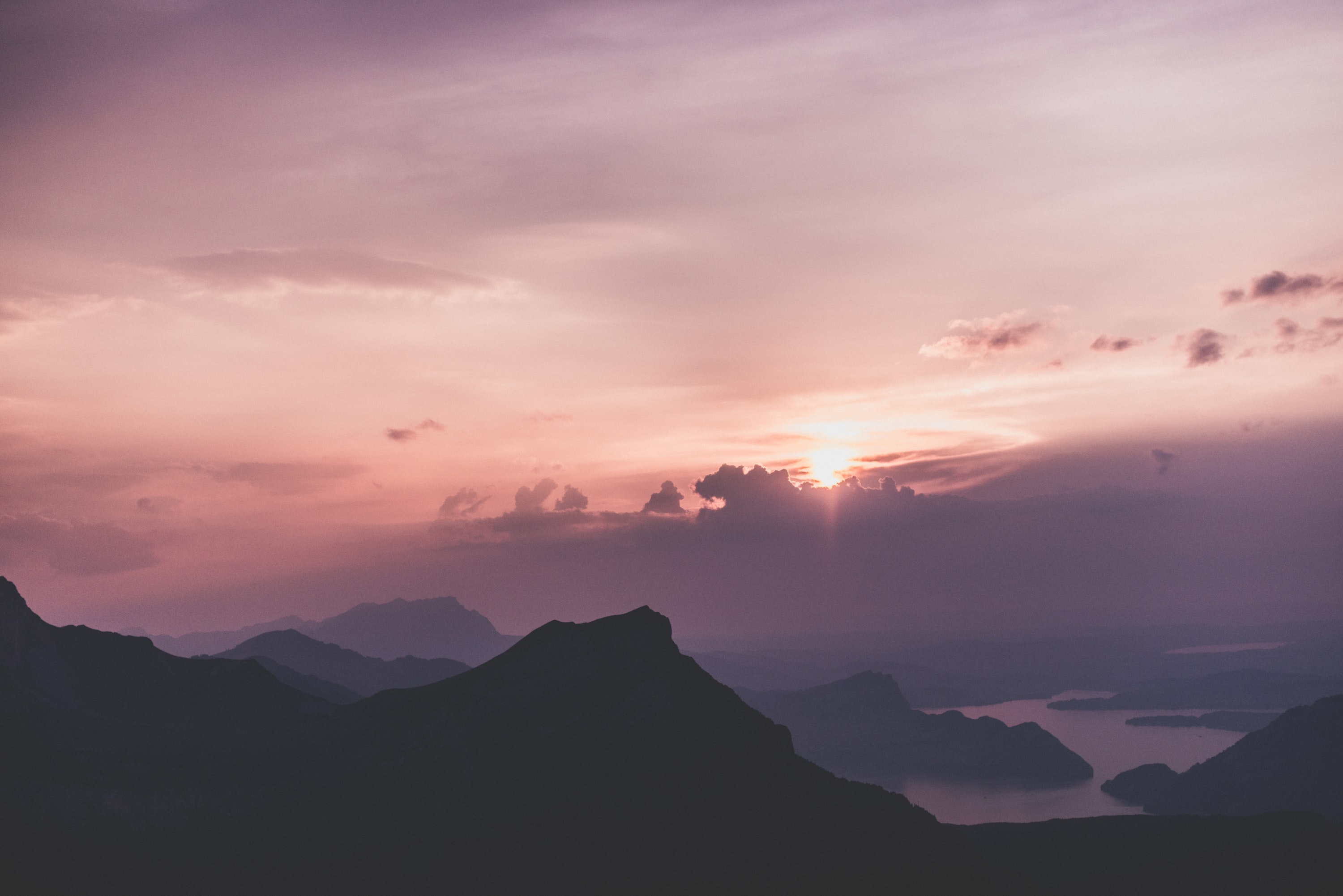 sunset, mountains, and body of water