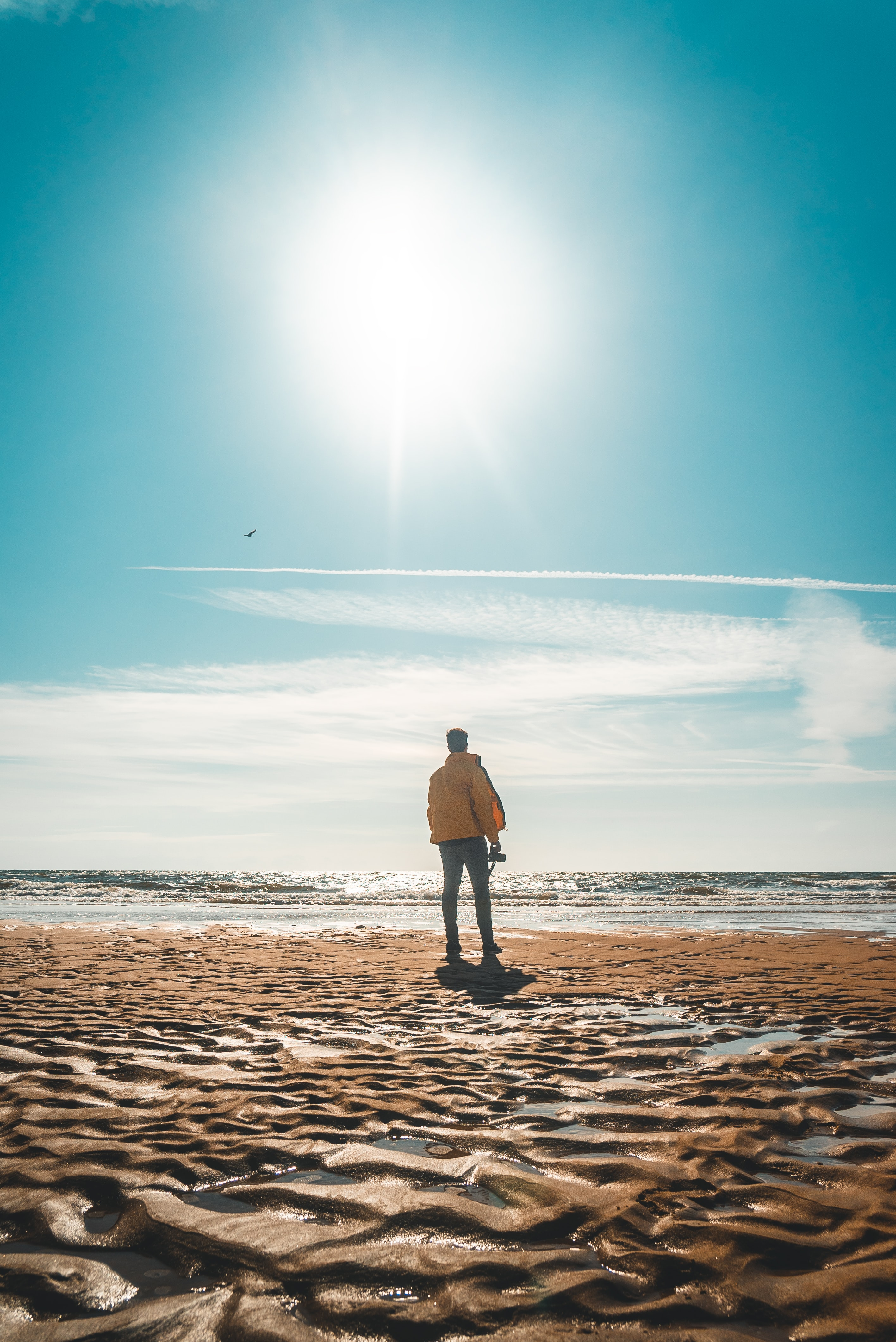 man in yellow jacket standing in front of shore