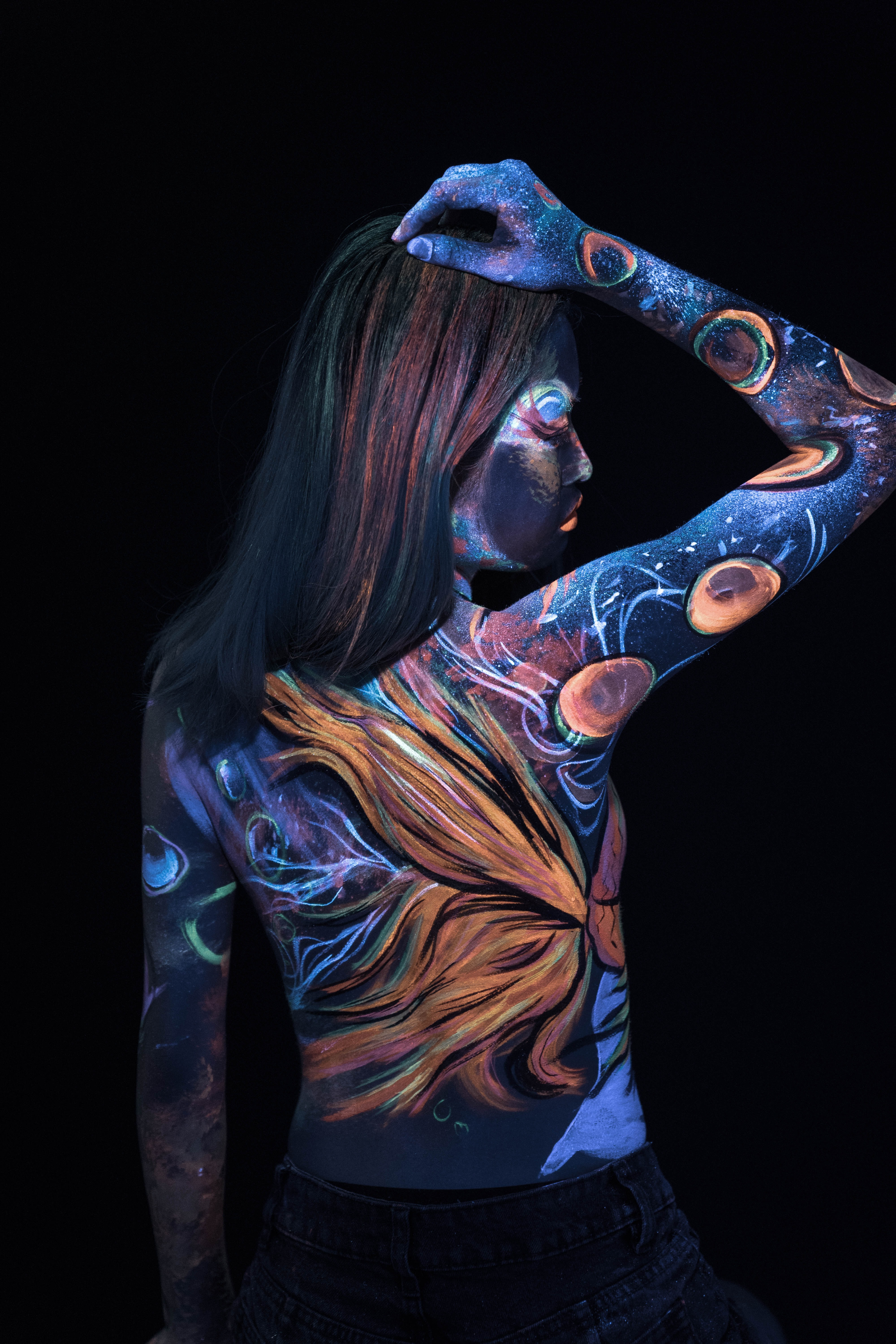woman with body tattoo standing in the dark