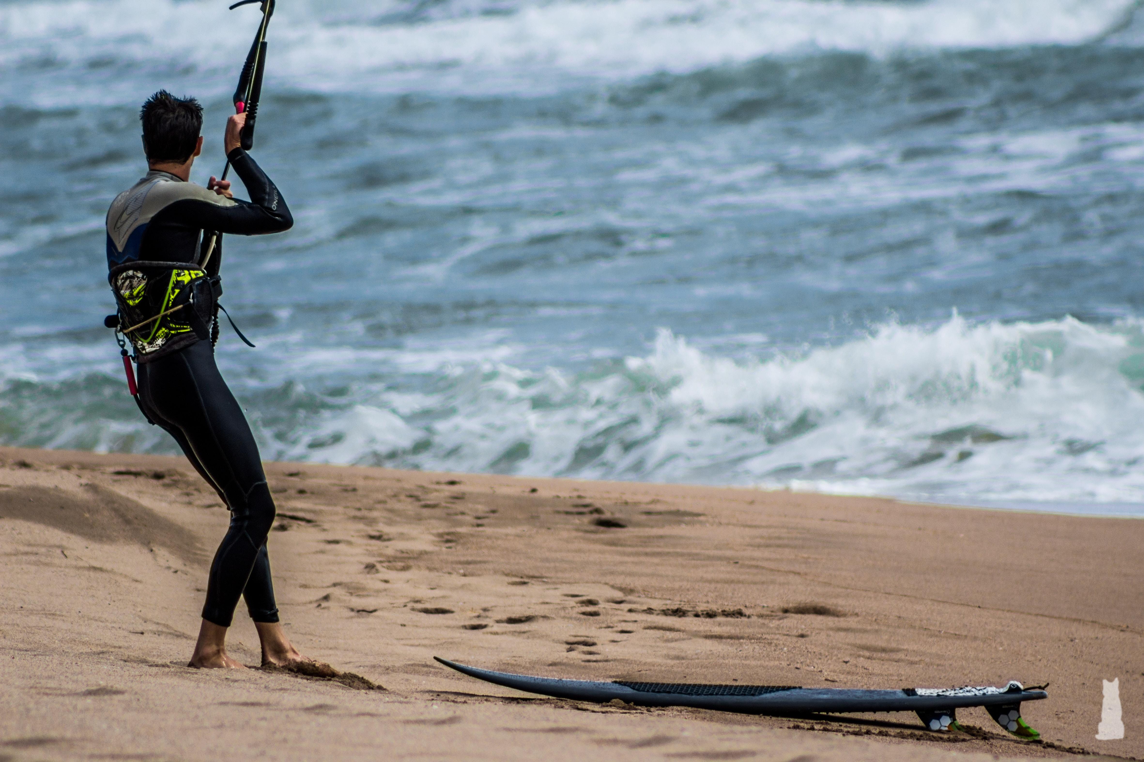 man in wet suit standing beside surfboard on seashore during daytime