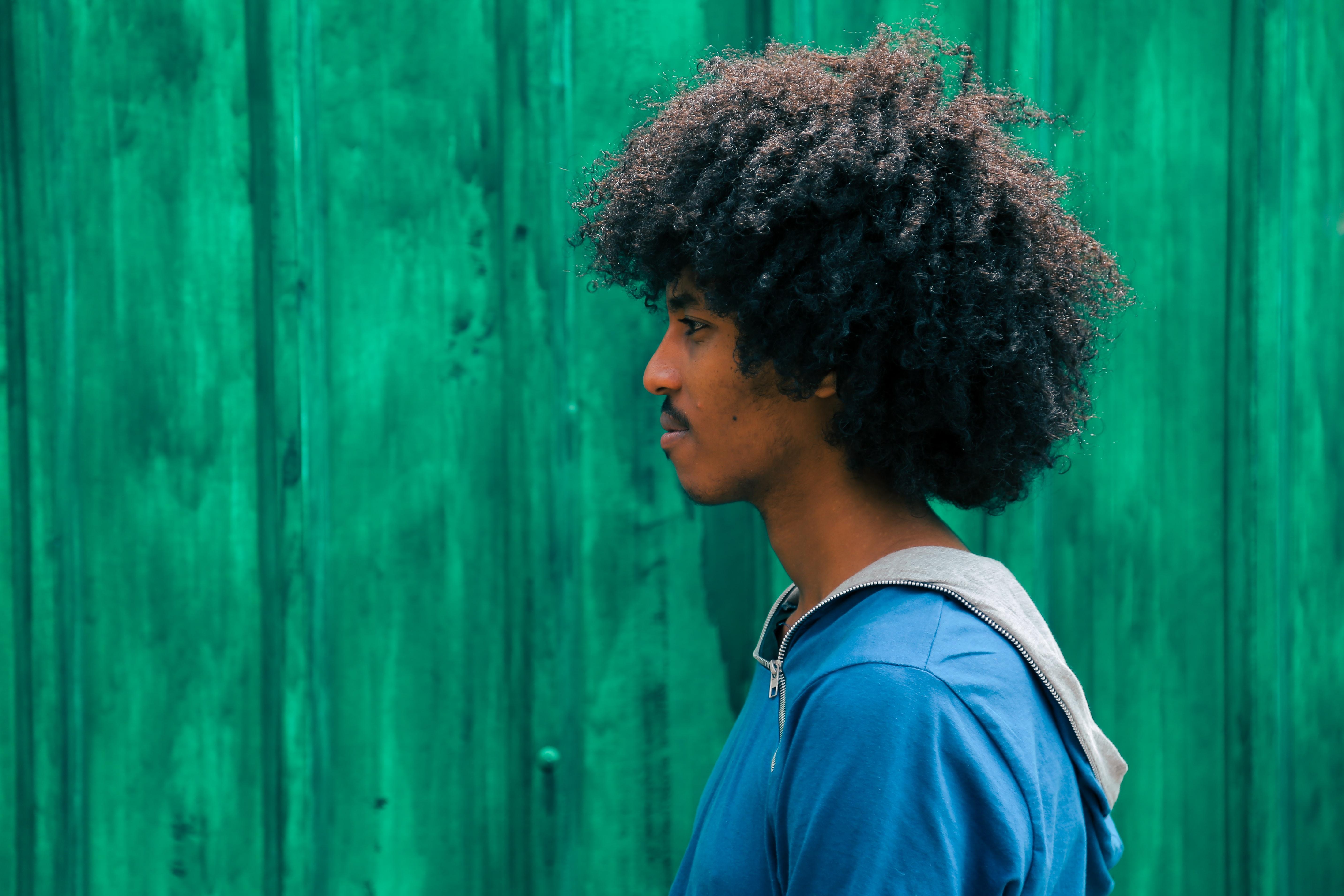 man facing right near green wall