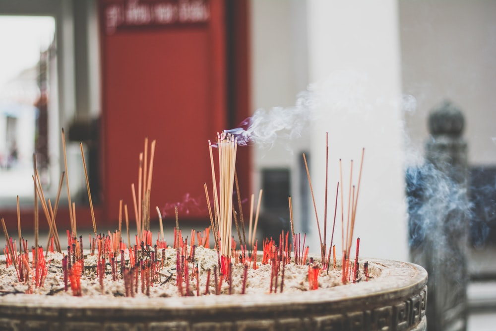 incense sticks on top of gray ashes