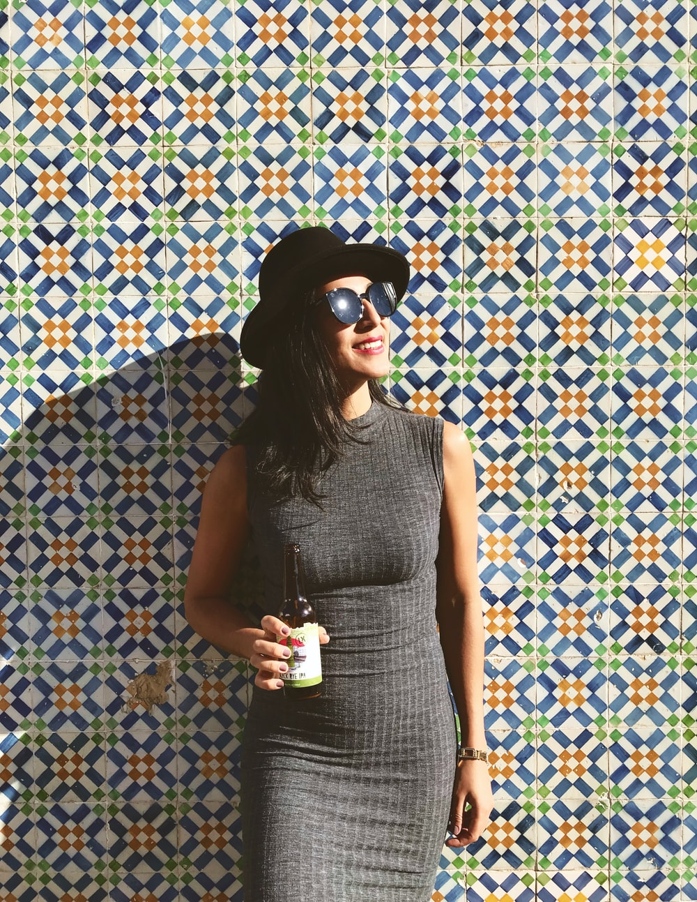 woman standing near the wall while holding beer bottle