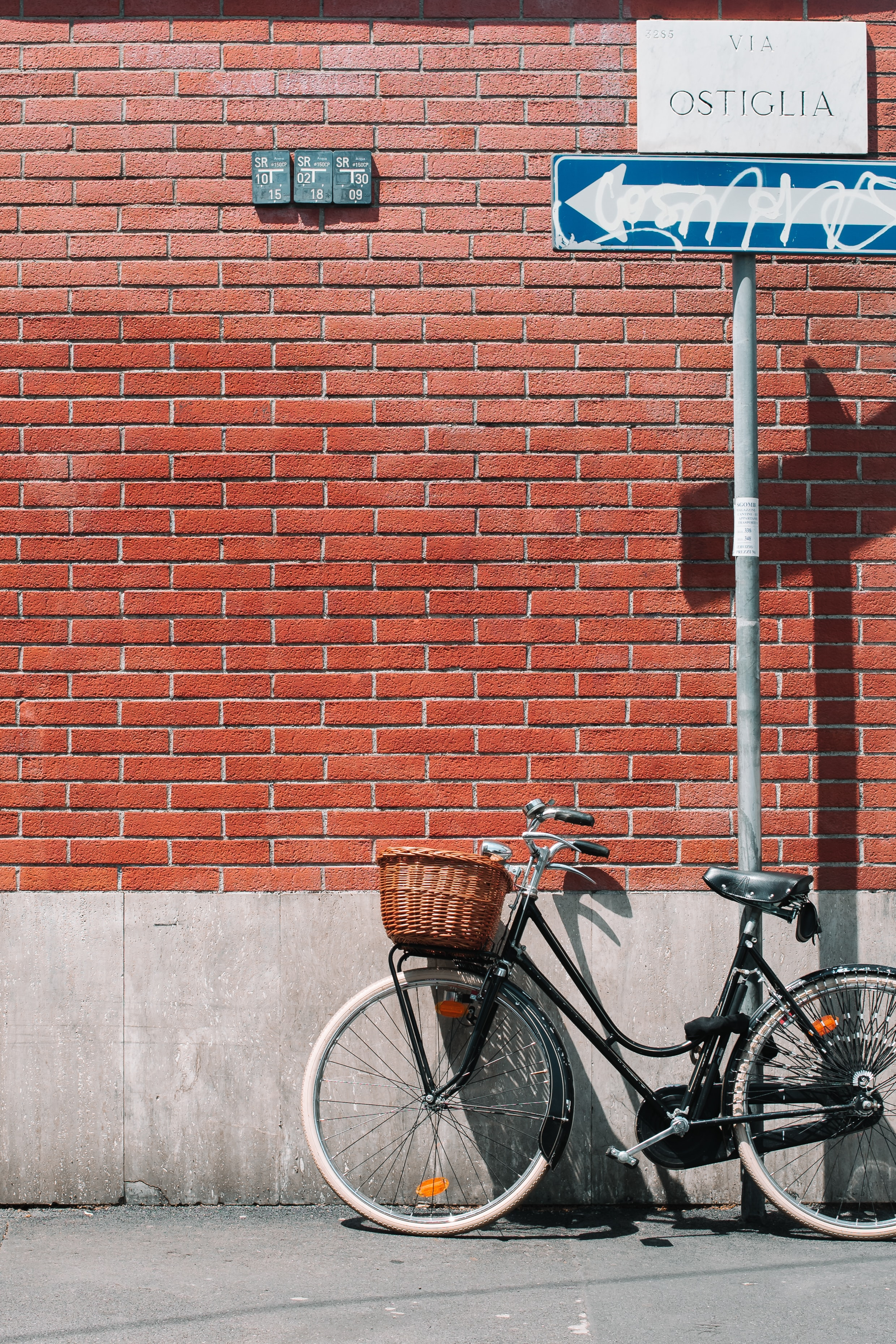 black cruiser bicycle leaning on gray steel post