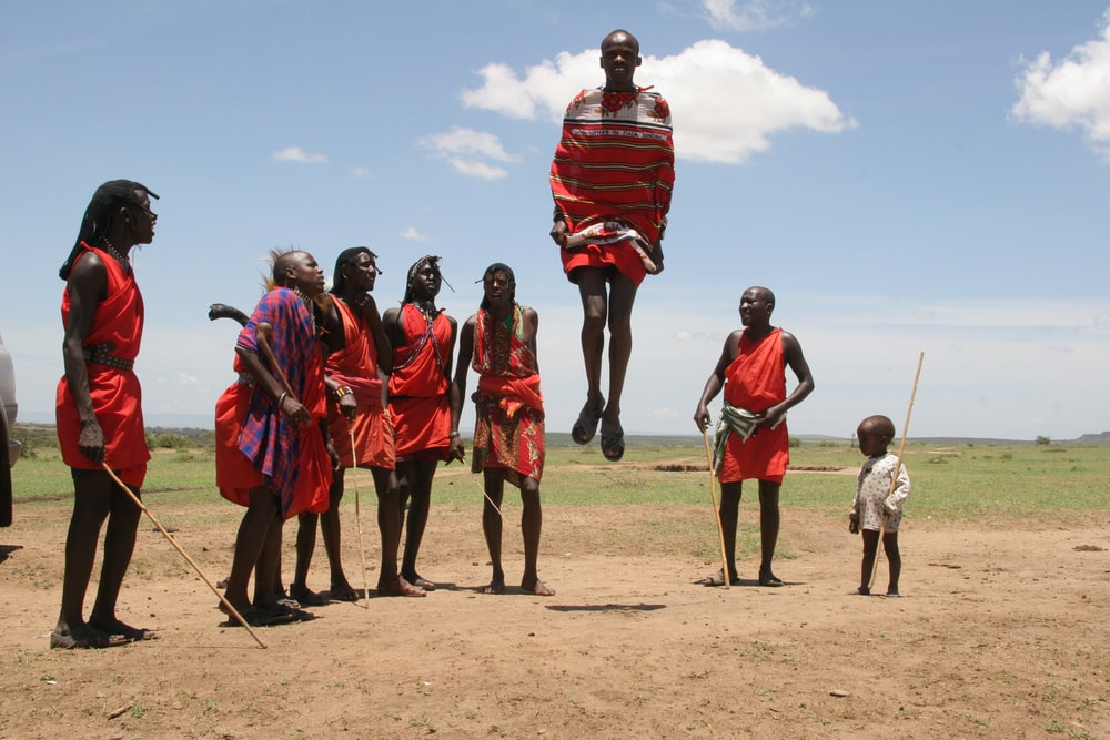 person in red dress jumping over brown soil
