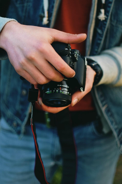 person holding black Canon DSLR camera