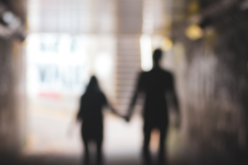 silhouette of man and woman holding hands