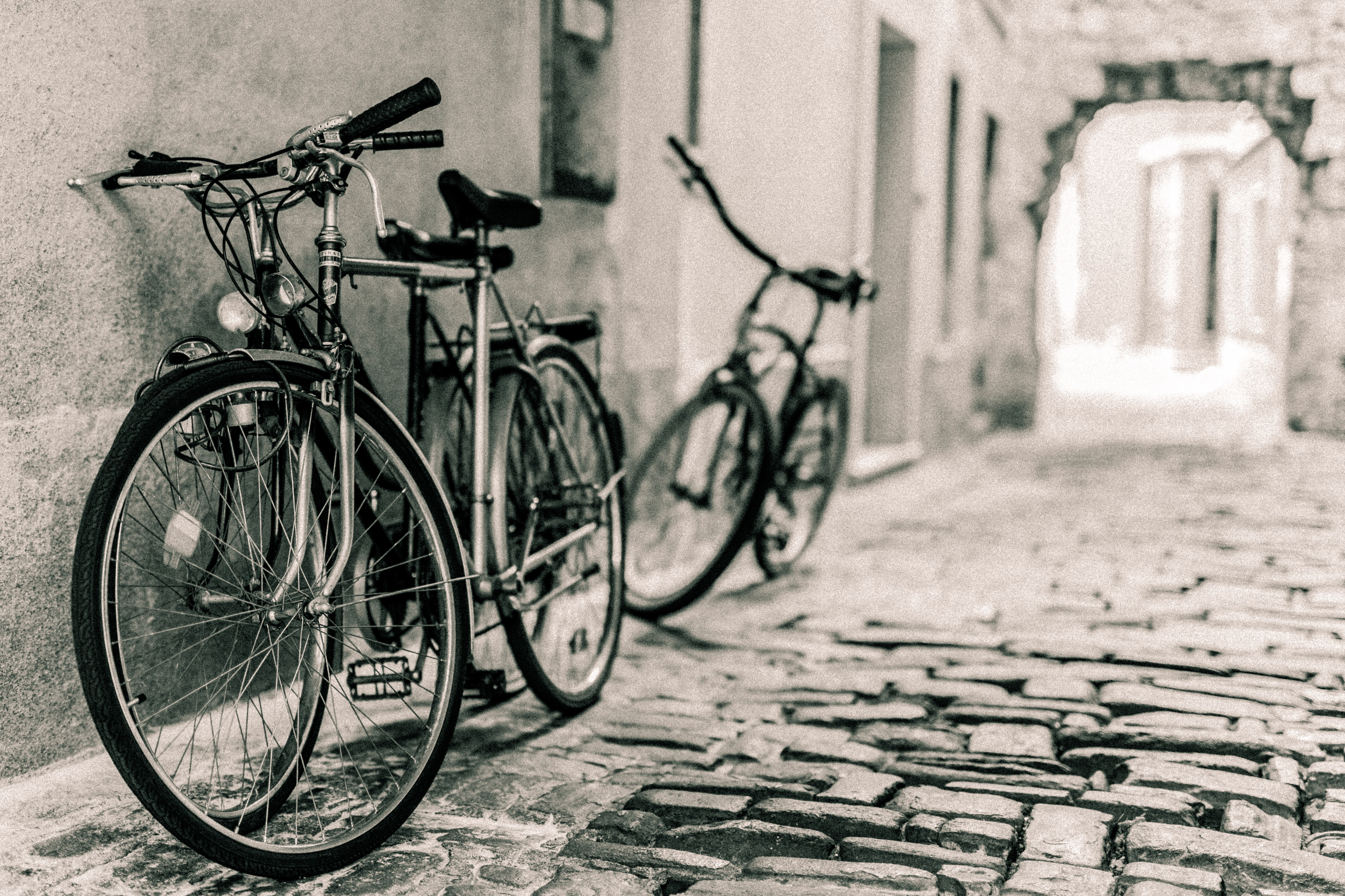 two bicycles leaning on alley way