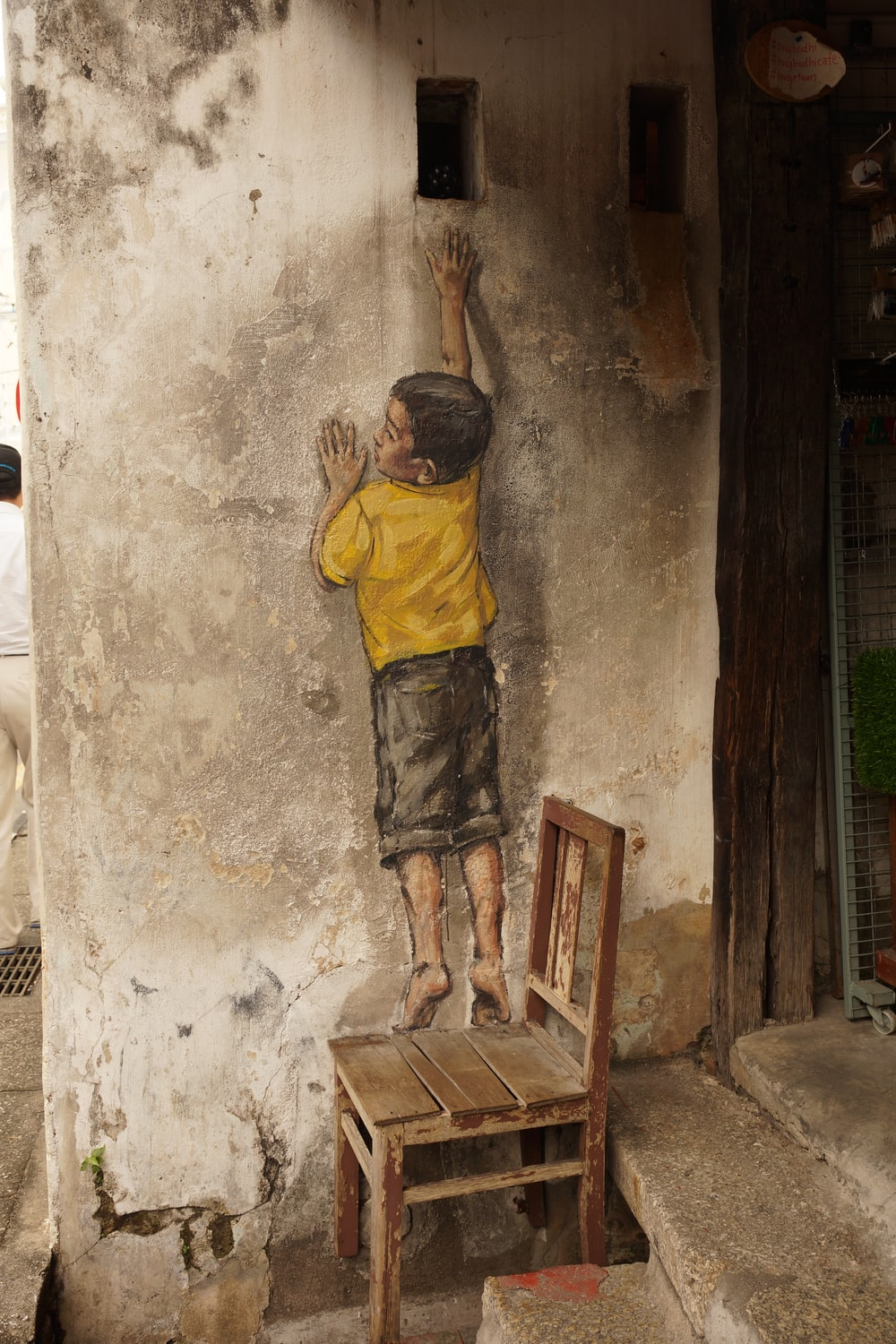 boy standing on wooden chair reaching hole on concrete wall painting