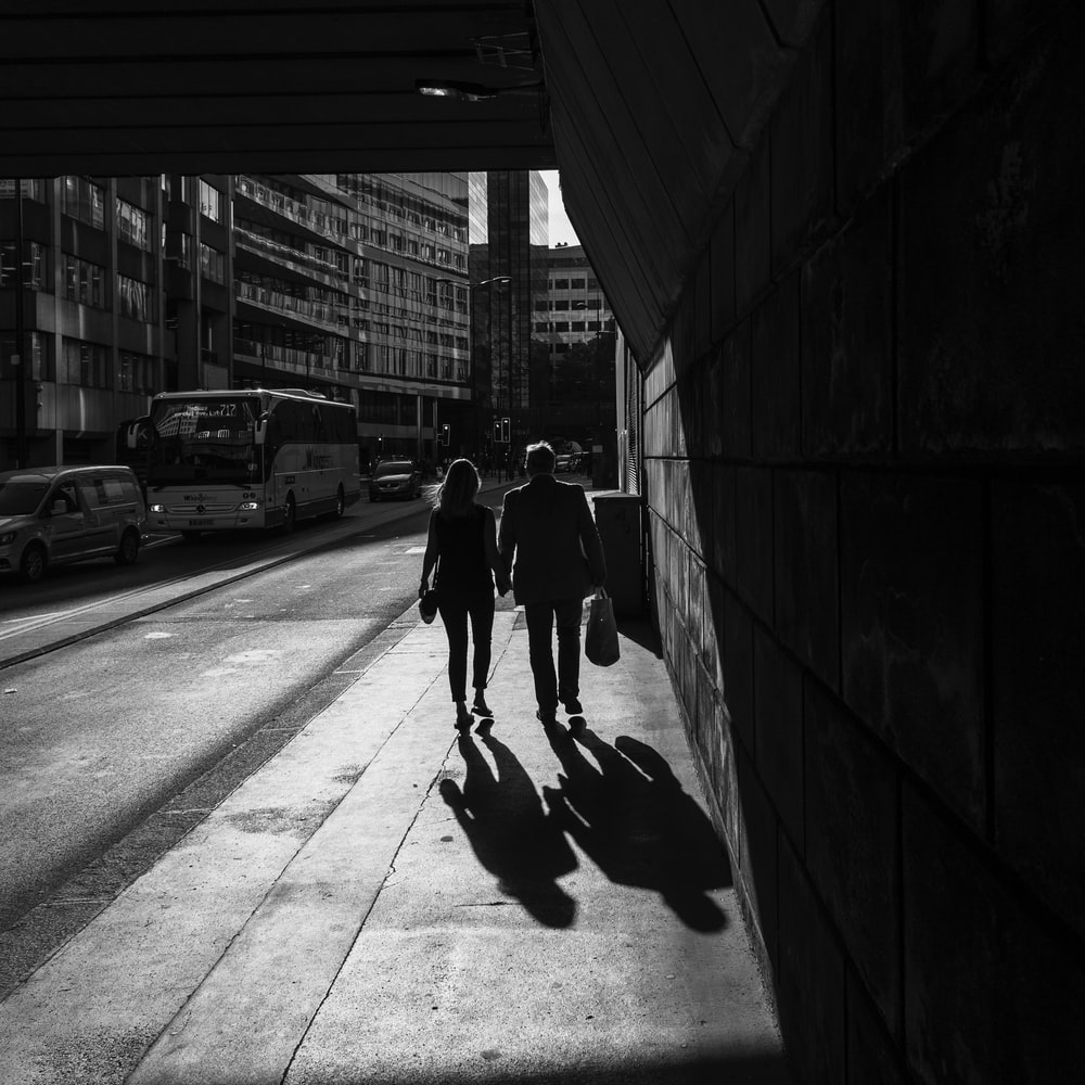 grayscale photography of man and woman walking on sidewalk