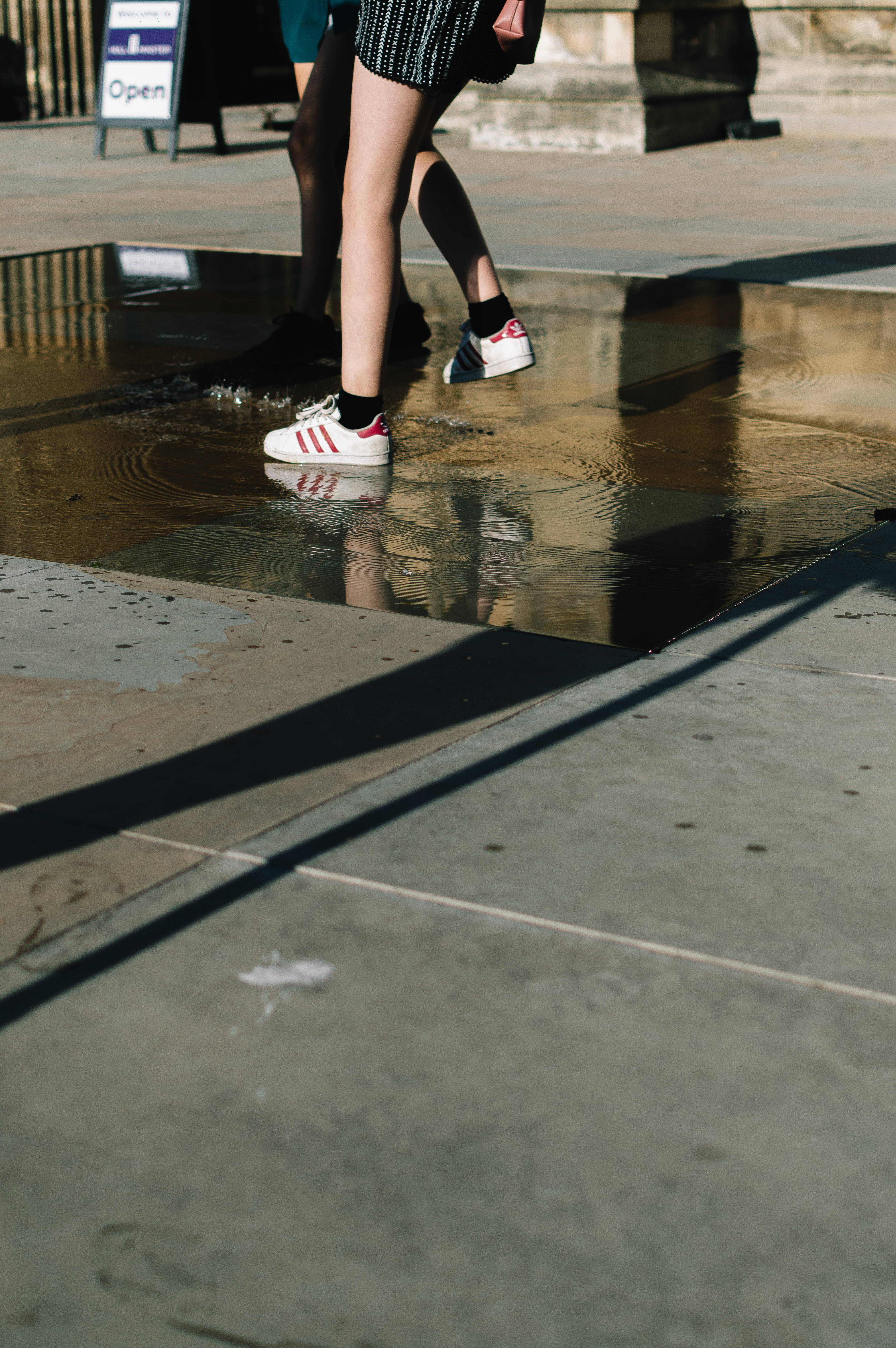 person wearing white-and-red adidas sneakers stepping on puddle of water