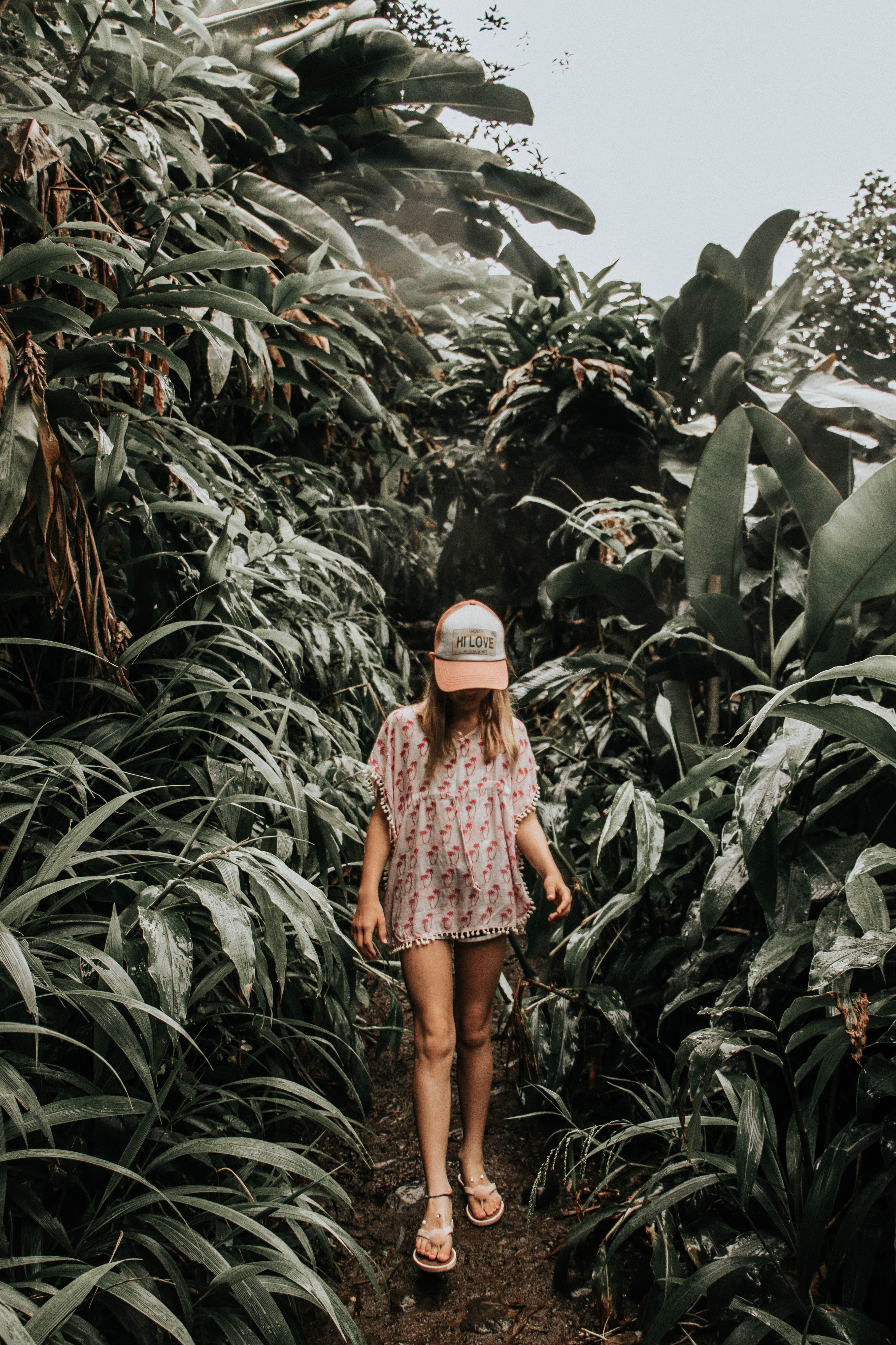 girl standing beside plants at daytime