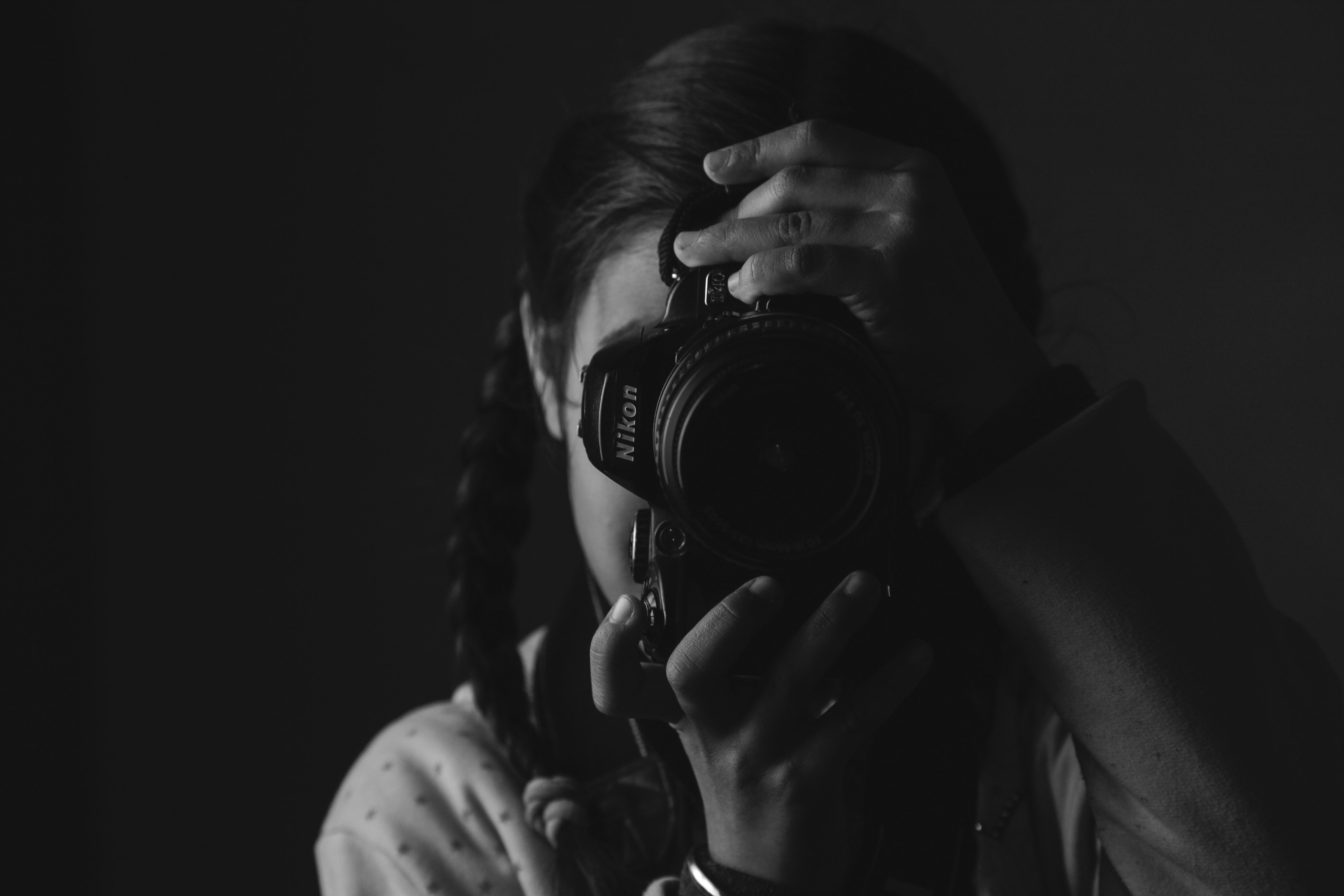 girl taking photo using Nikon DSLR camera in grayscale photography