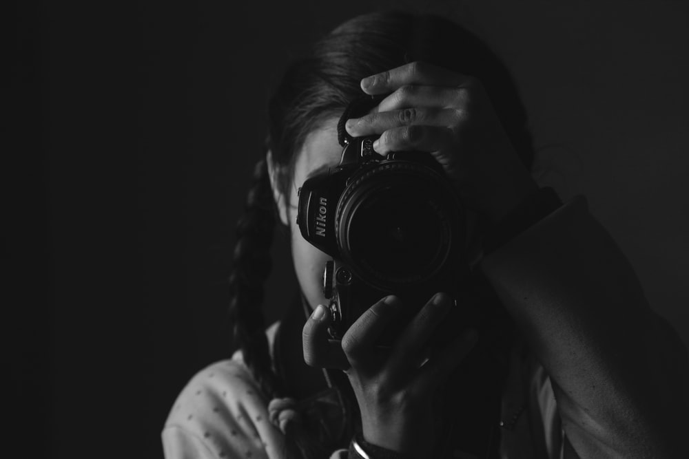 girl taking photo using Nikon DSLR camera in grayscale photography