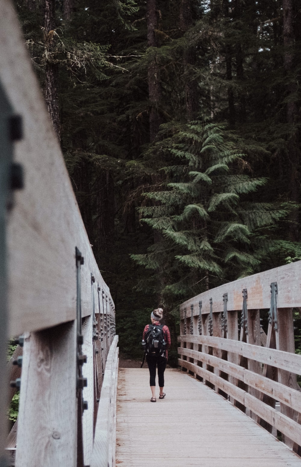 woman walking on brown wooden bridge